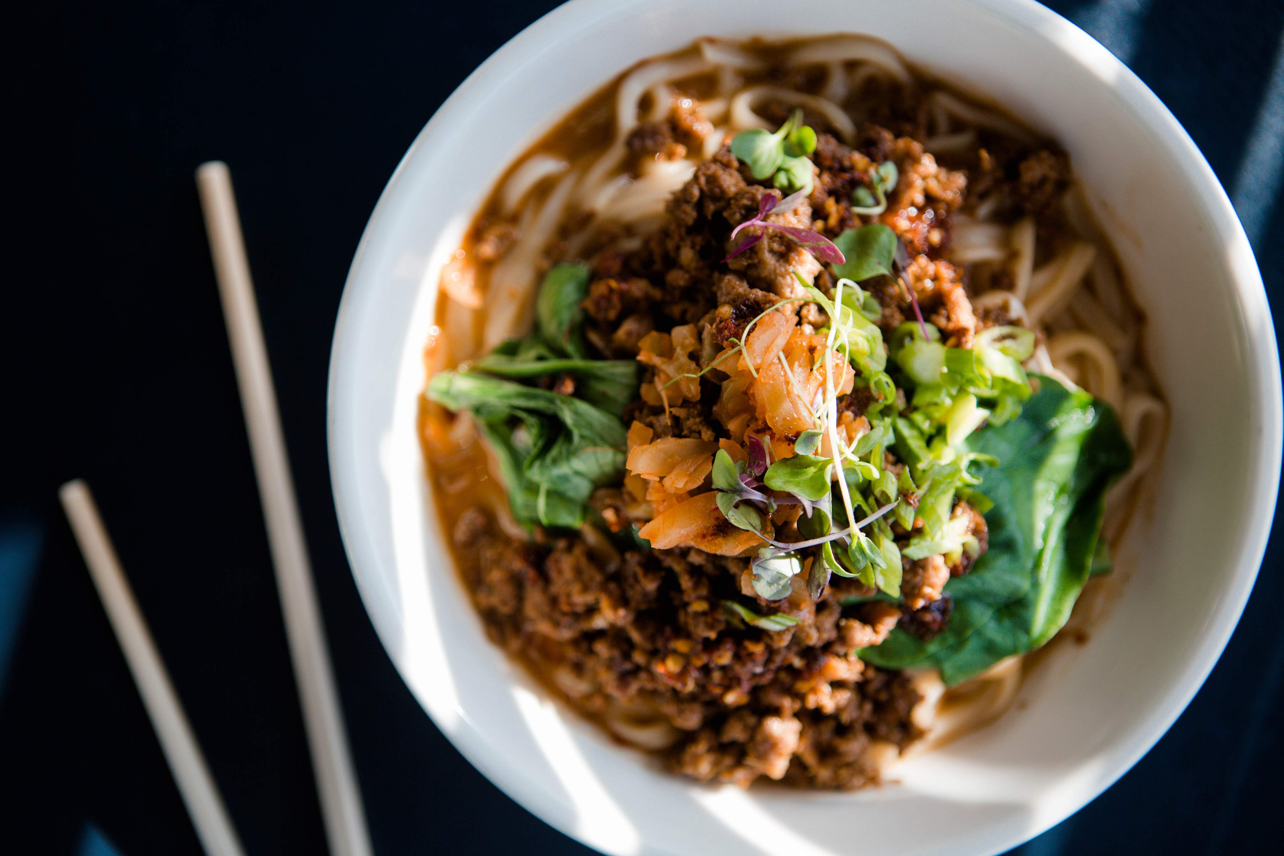 Dan Dan noodles in a bowl at Lionhead, with chopsticks to the left.