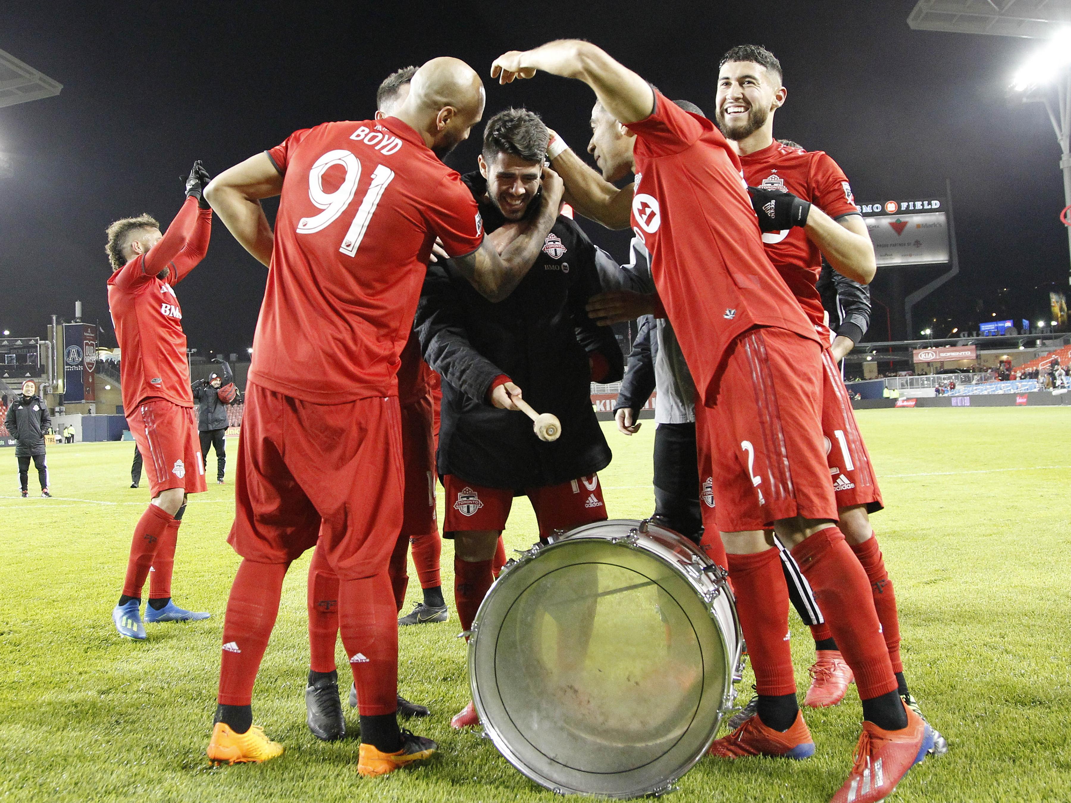 Toronto FC forward Alejandro Pozuelo (center black jacket) celebrates a win over New York City FC by banging on a fan's drum at BMO Field.