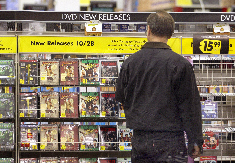 A shopper peruses a shelf of DVDs.
