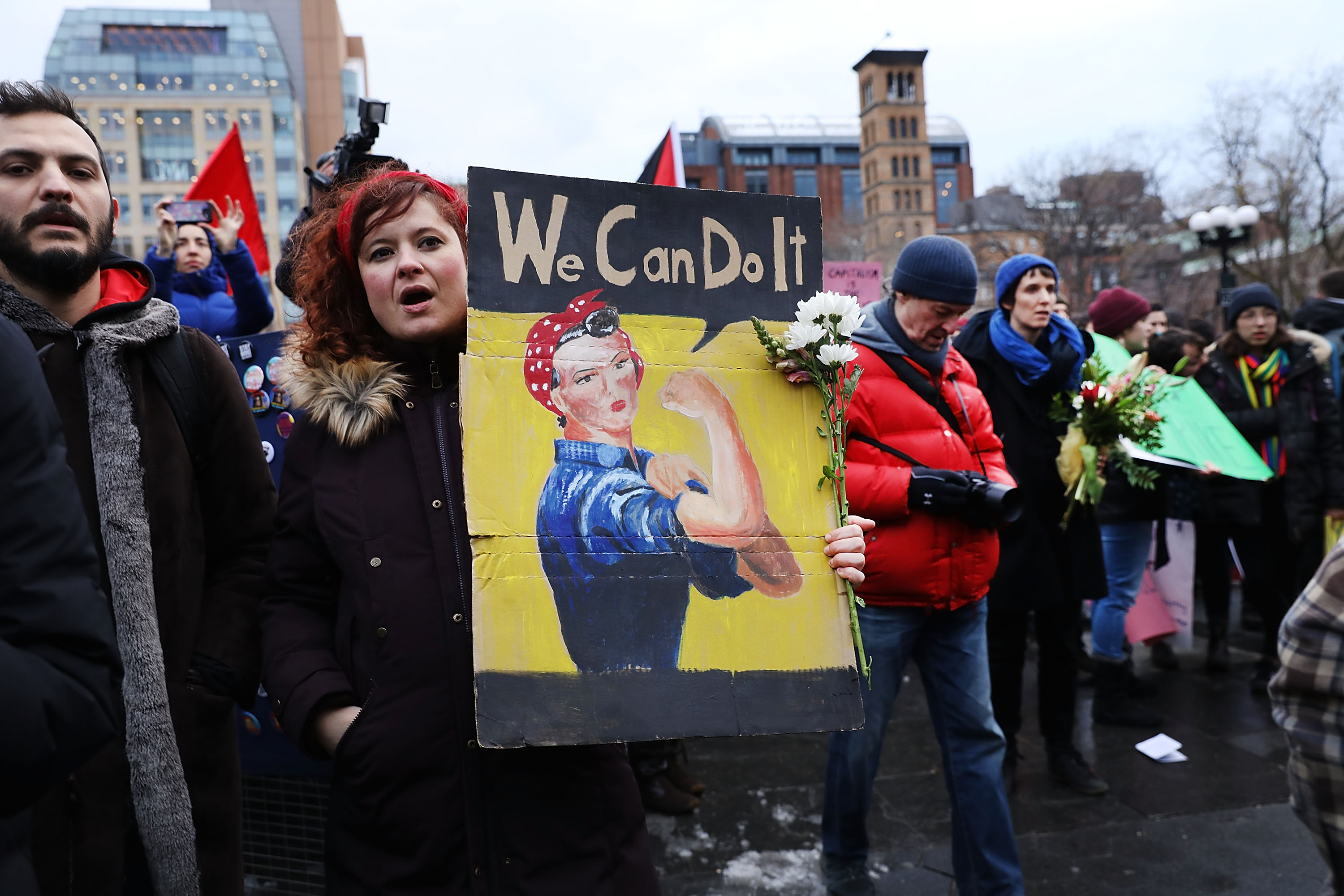 """A woman at a rally holds a sign reading """"We can do it"""" with a picture of Rosie the Riveter."""