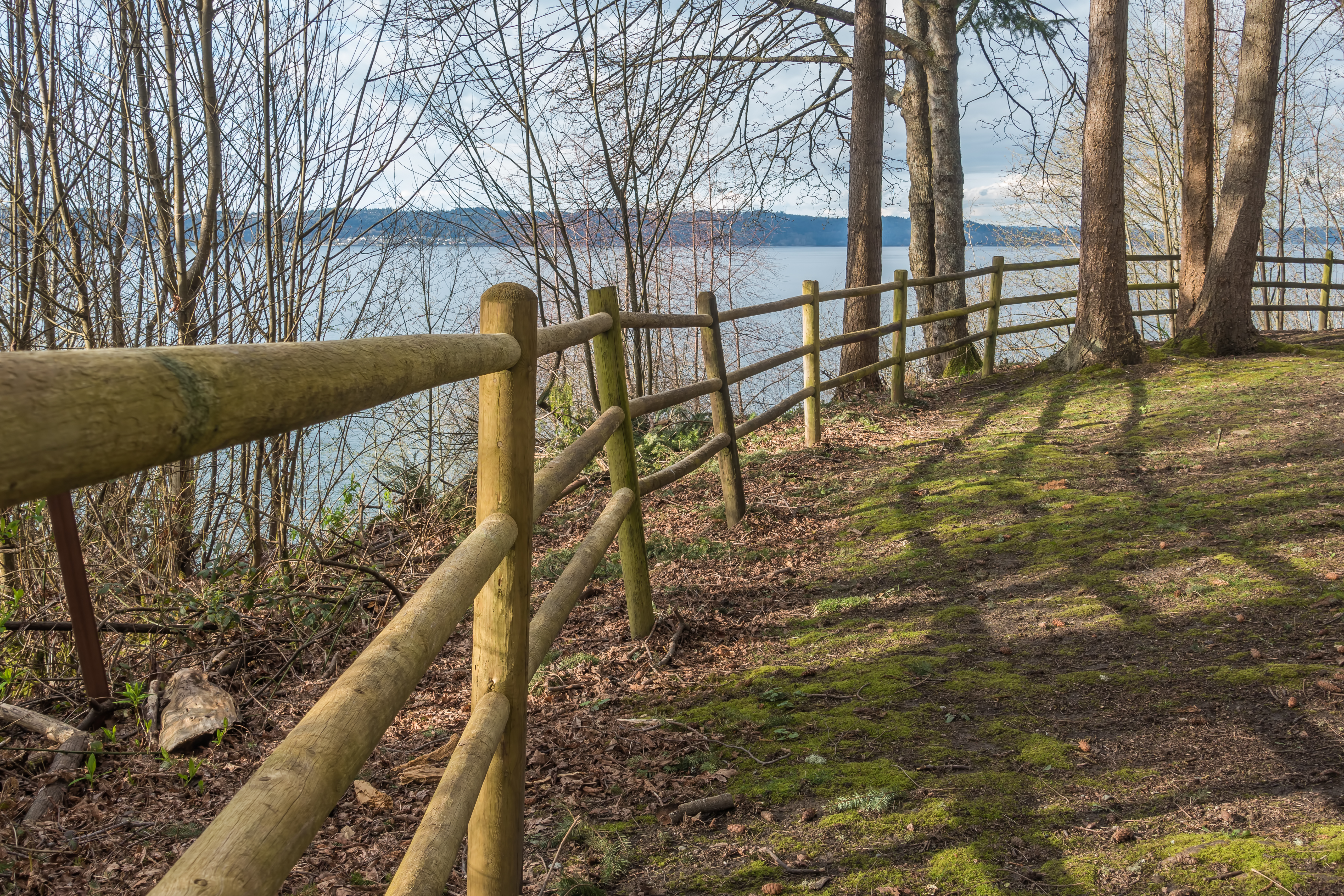 A log fence curves along the side of a bluff with a view of water, with mountains in the distance.
