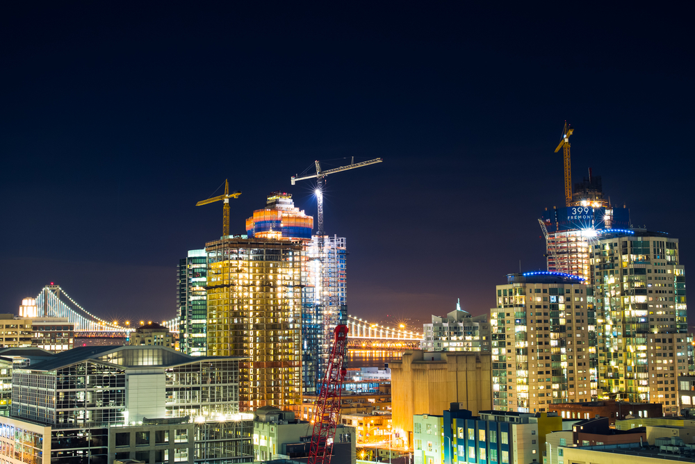 Construction cranes on top of San Francisco rooftops at night.