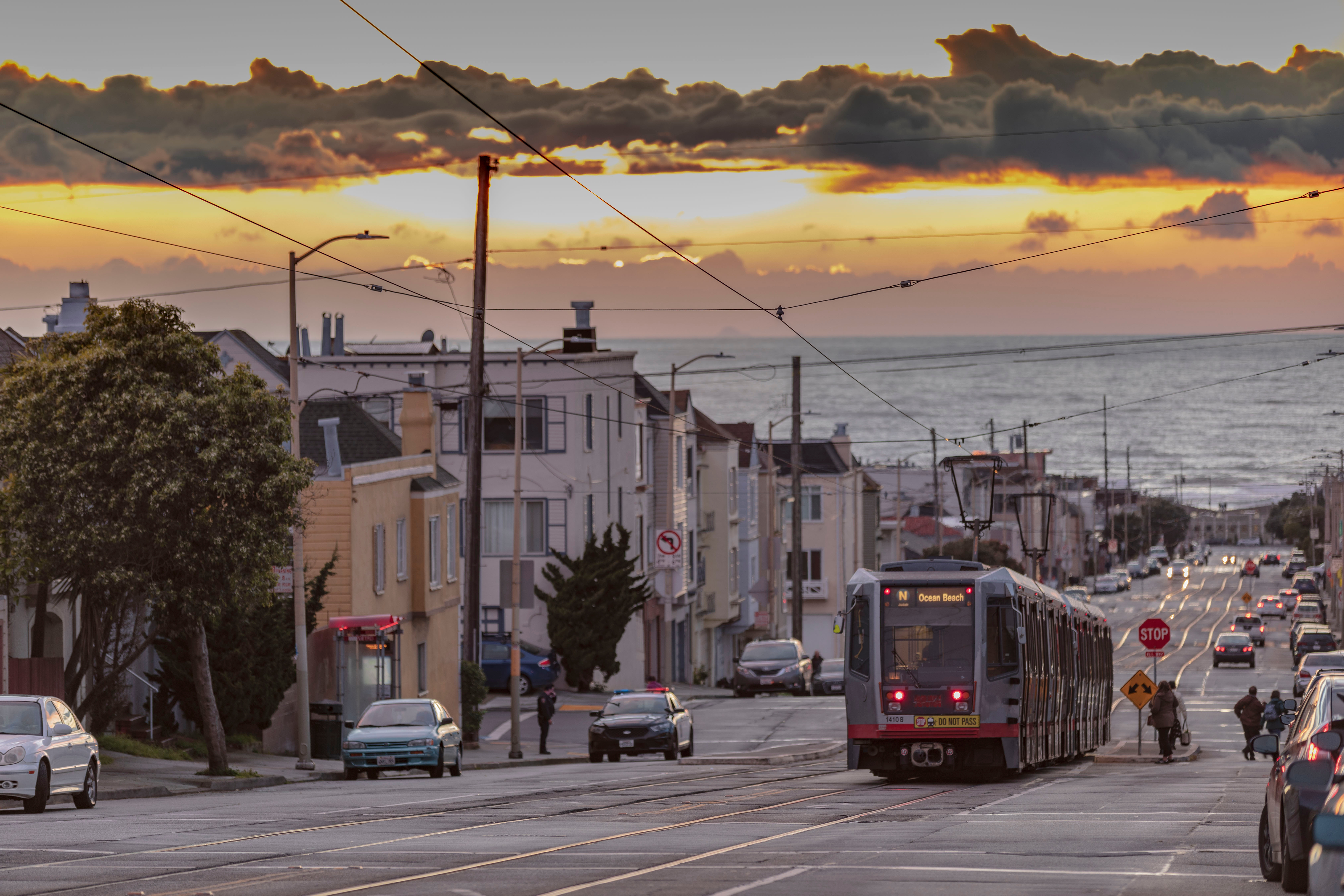 A sunset breaks through gray clouds above a street with a gray streetcar and homes.