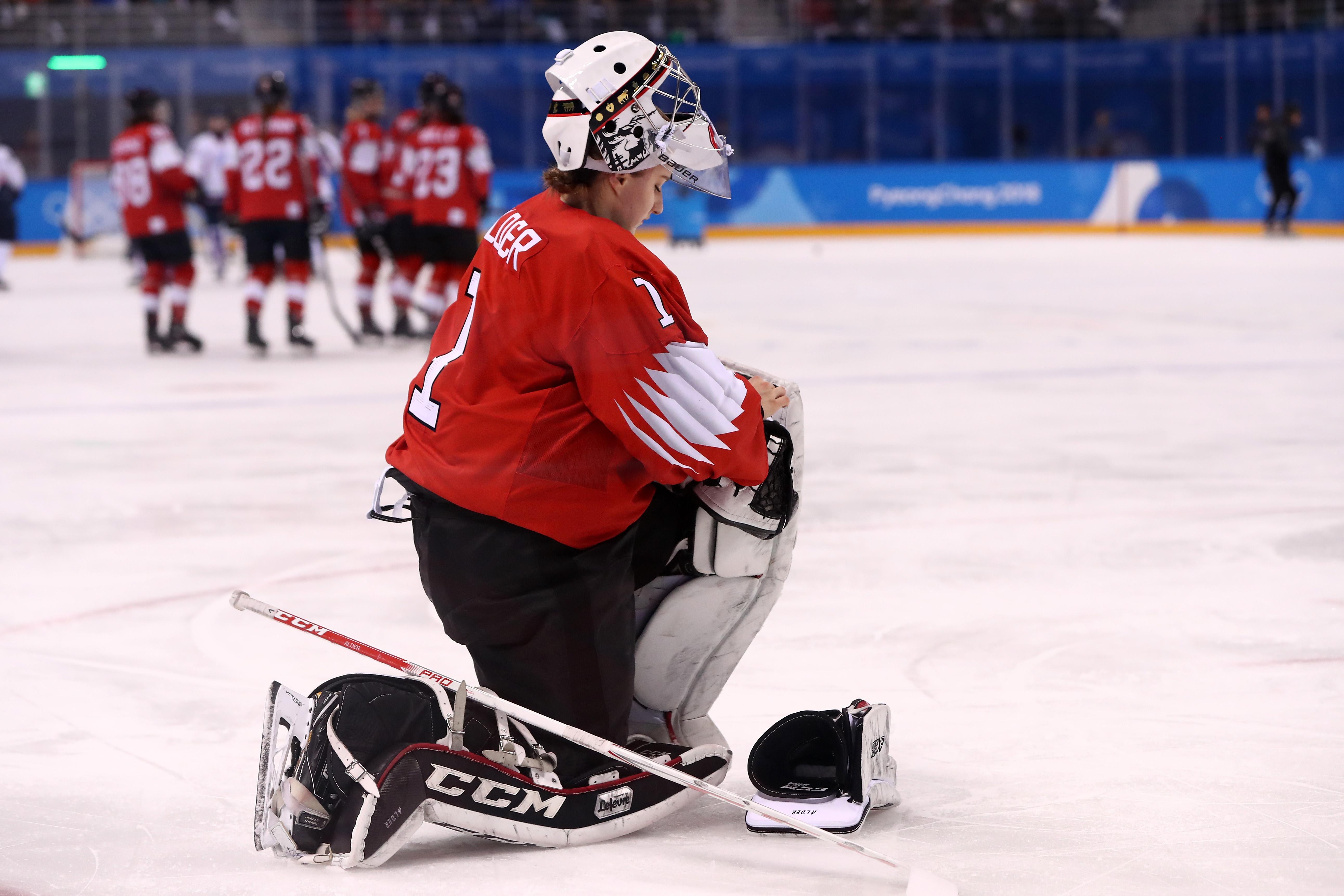 Janine Alder #1 of Switzerlandkneels on the ice with her mask raised.