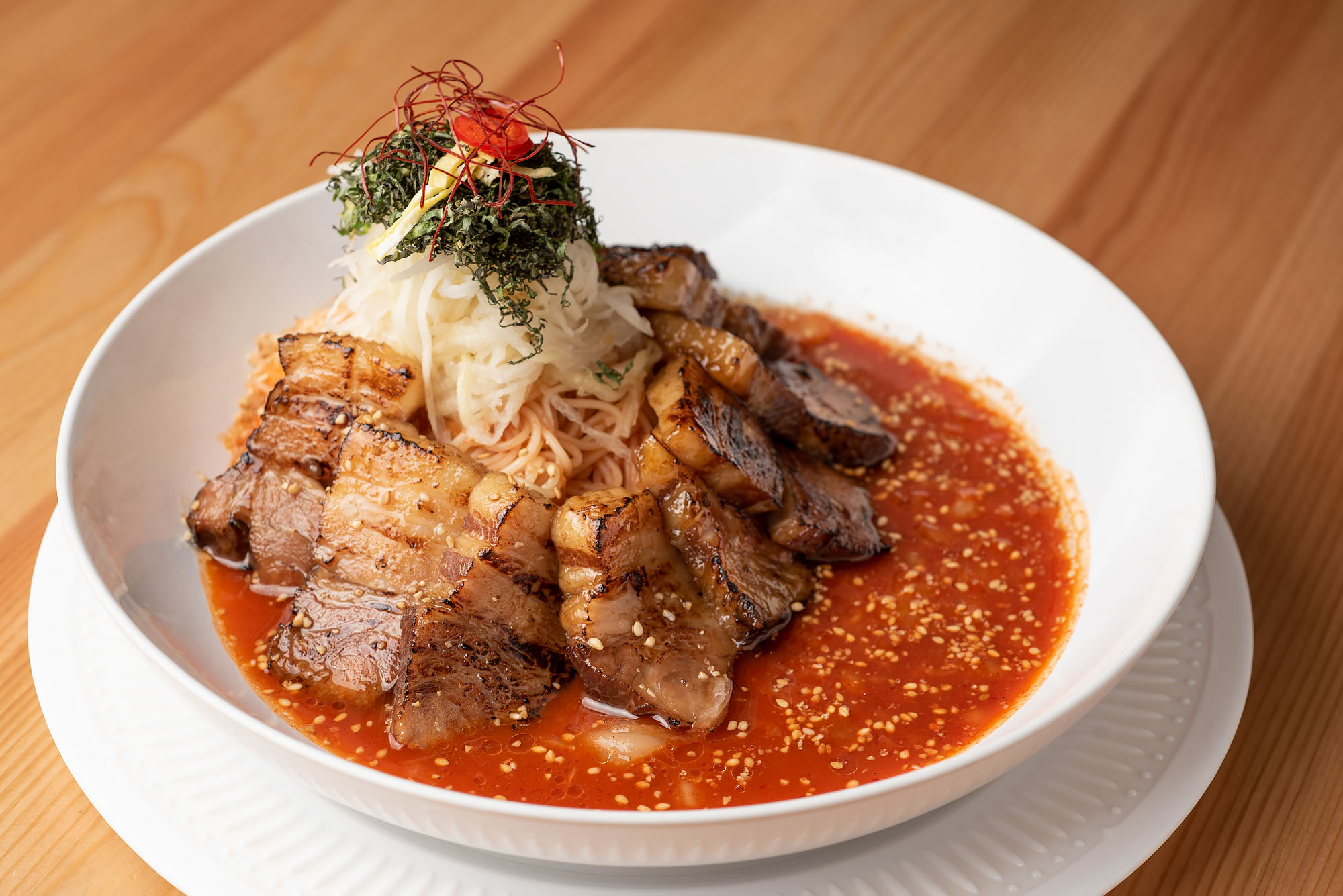 A pork belly dish sitting in bright red sauce in a white bowl.