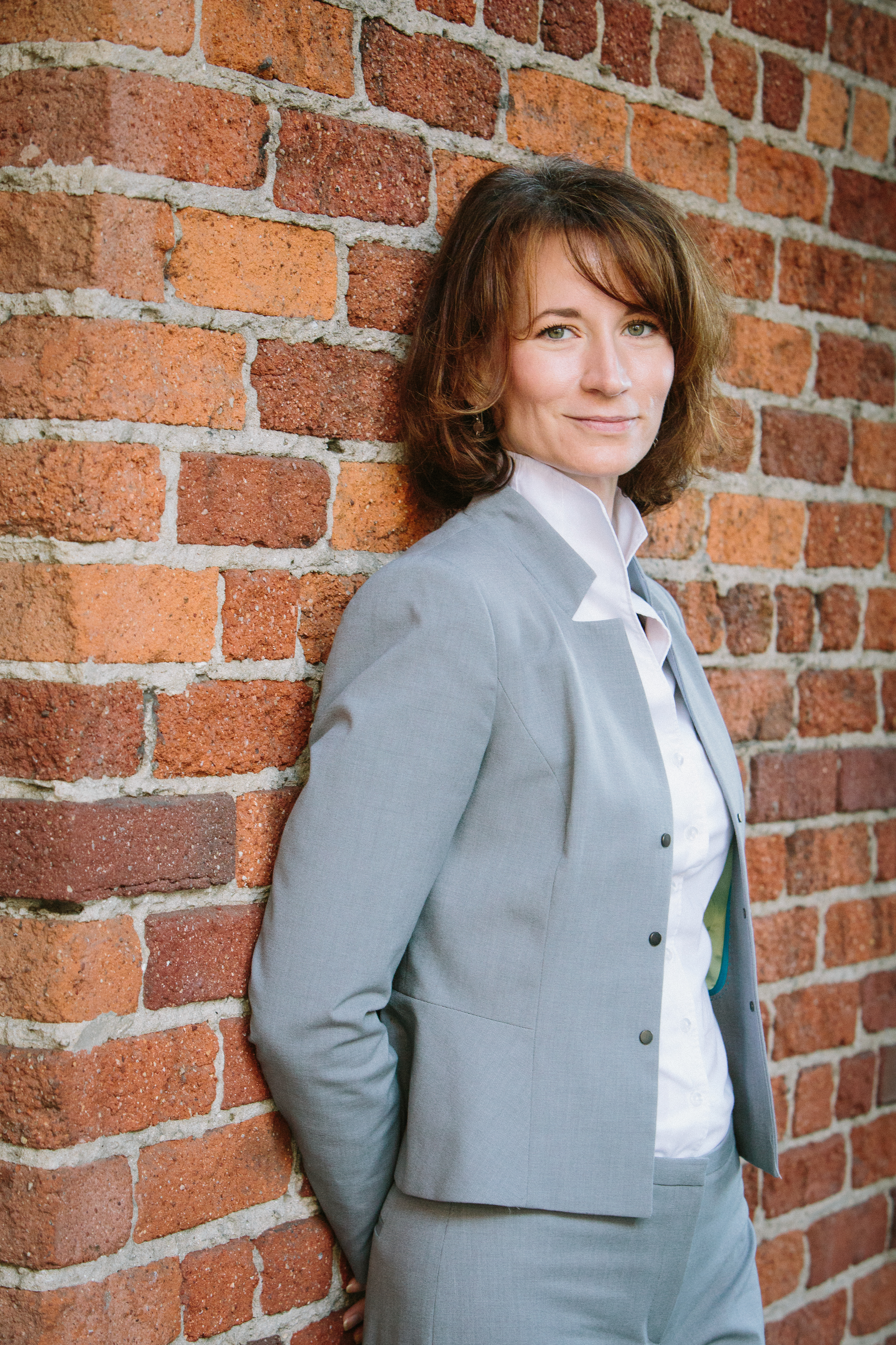 Pam Kostka, the new CEO of All Raise, standing in front of a brick wall.