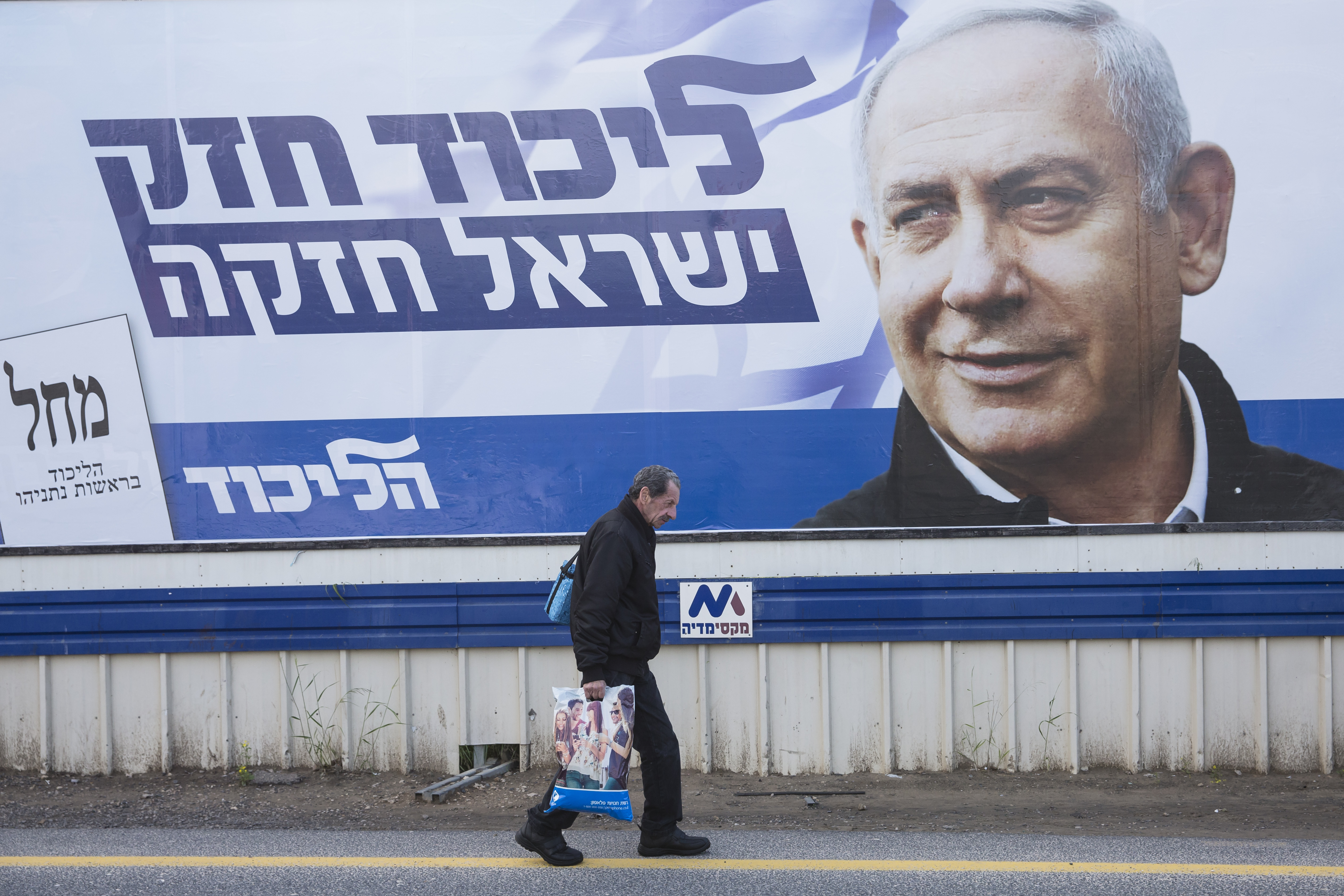 A man passes by a Likud party election campaign poster showing its leader Israeli Prime Minster Benjamin Netanyahu on April 1, 2019 in the city of Haedera, Israel.