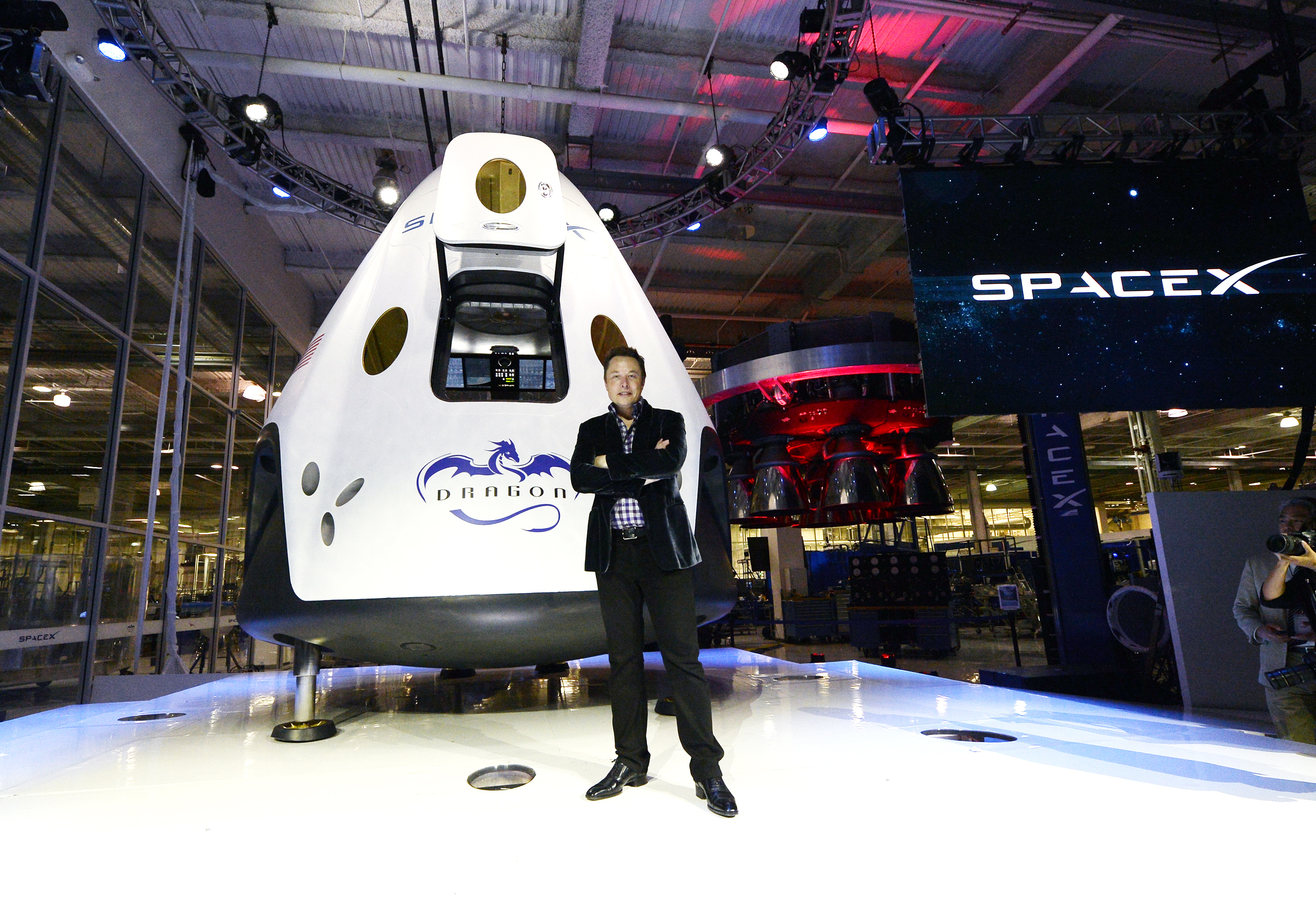 SpaceX CEO Elon Musk standing in front of the company's manned spacecraft, The Dragon V2.