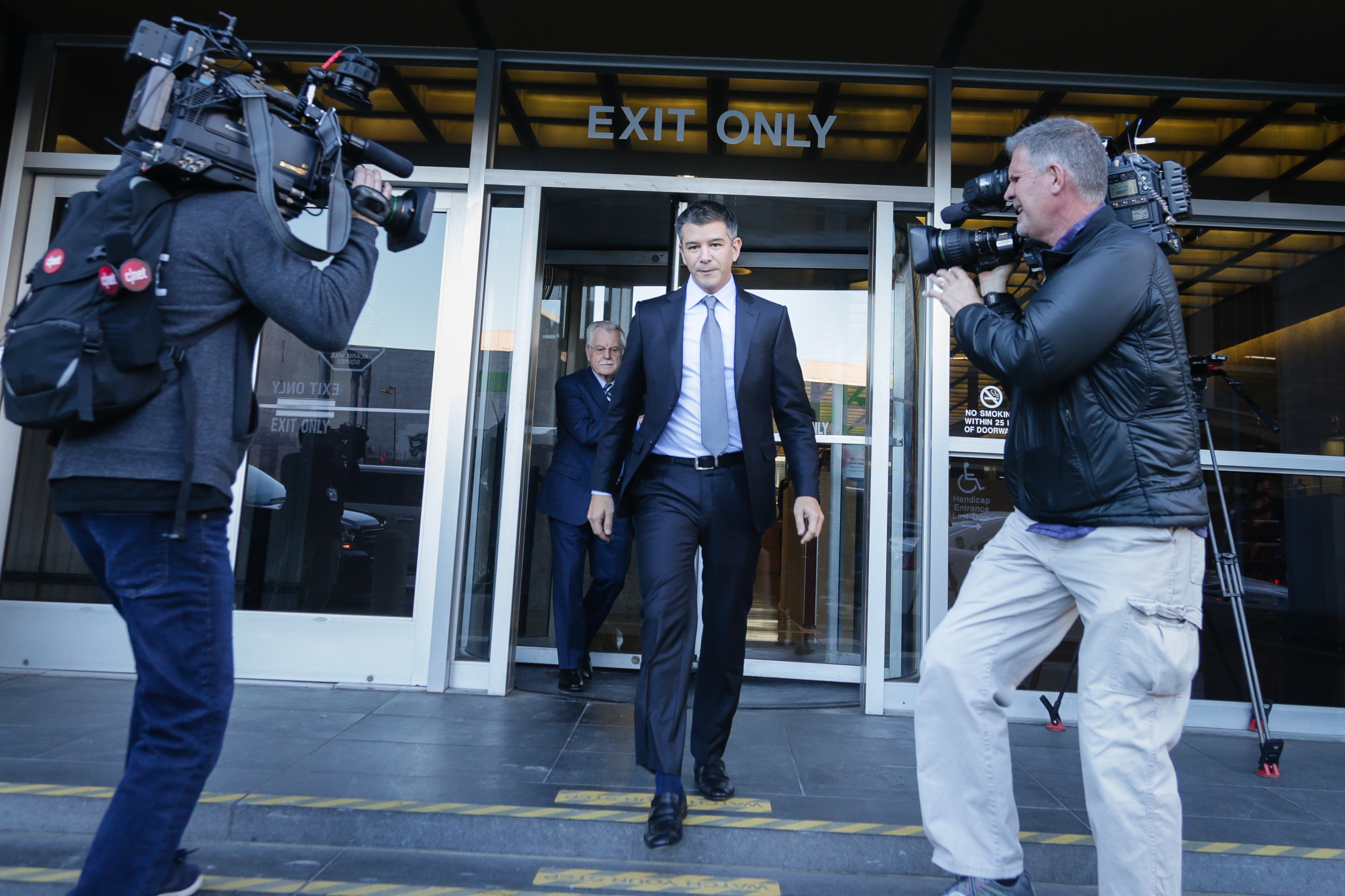 Travis Kalanick, Uber's founder and ex-CEO, being confronted with TV cameras as he walks out of the courthouse.