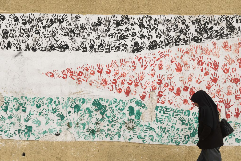 A woman passes in front of the graffiti with a flag of Palestine in the city center of Amman.