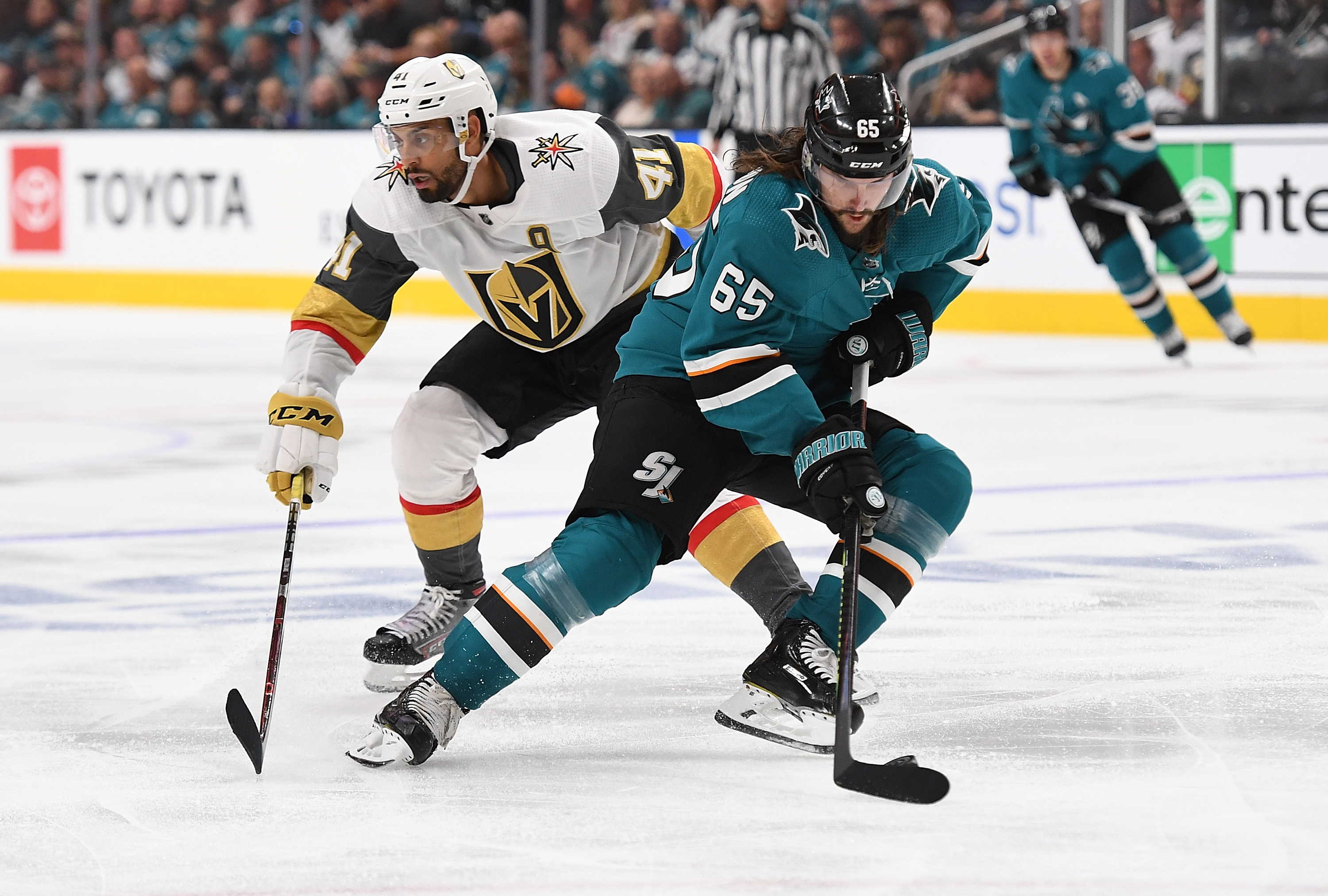 SAN JOSE, CA - APRIL 12: Erik Karlsson #65 of the San Jose Sharks skate with control of the puck keeping it away from Pierre-Edouard Bellemare #41 of the Vegas Golden Knights during the third period in Game Two of the Western Conference First Round during