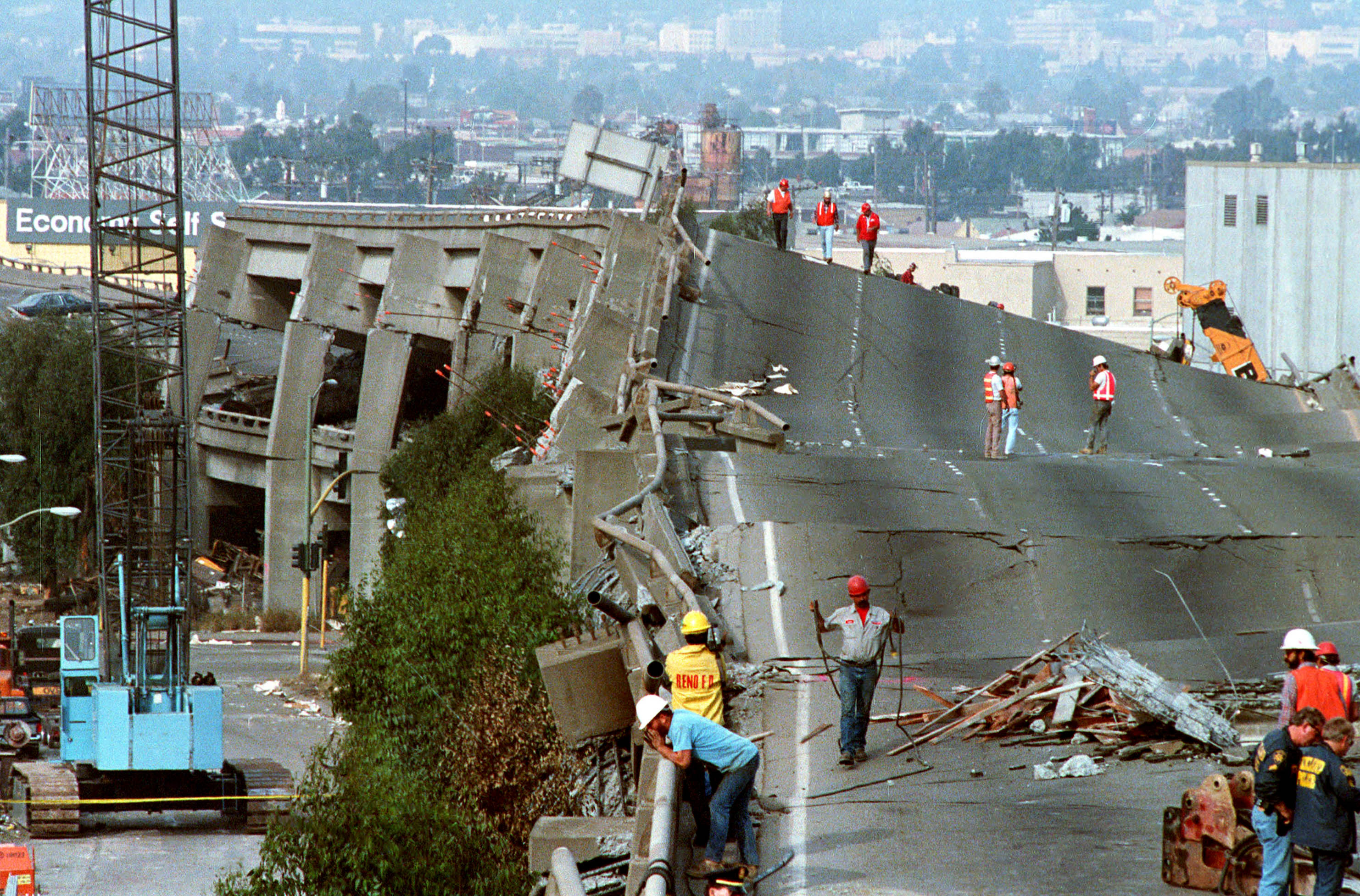 Rescue workers in hardhats walking on a crumbling multiple-leveled freeway.