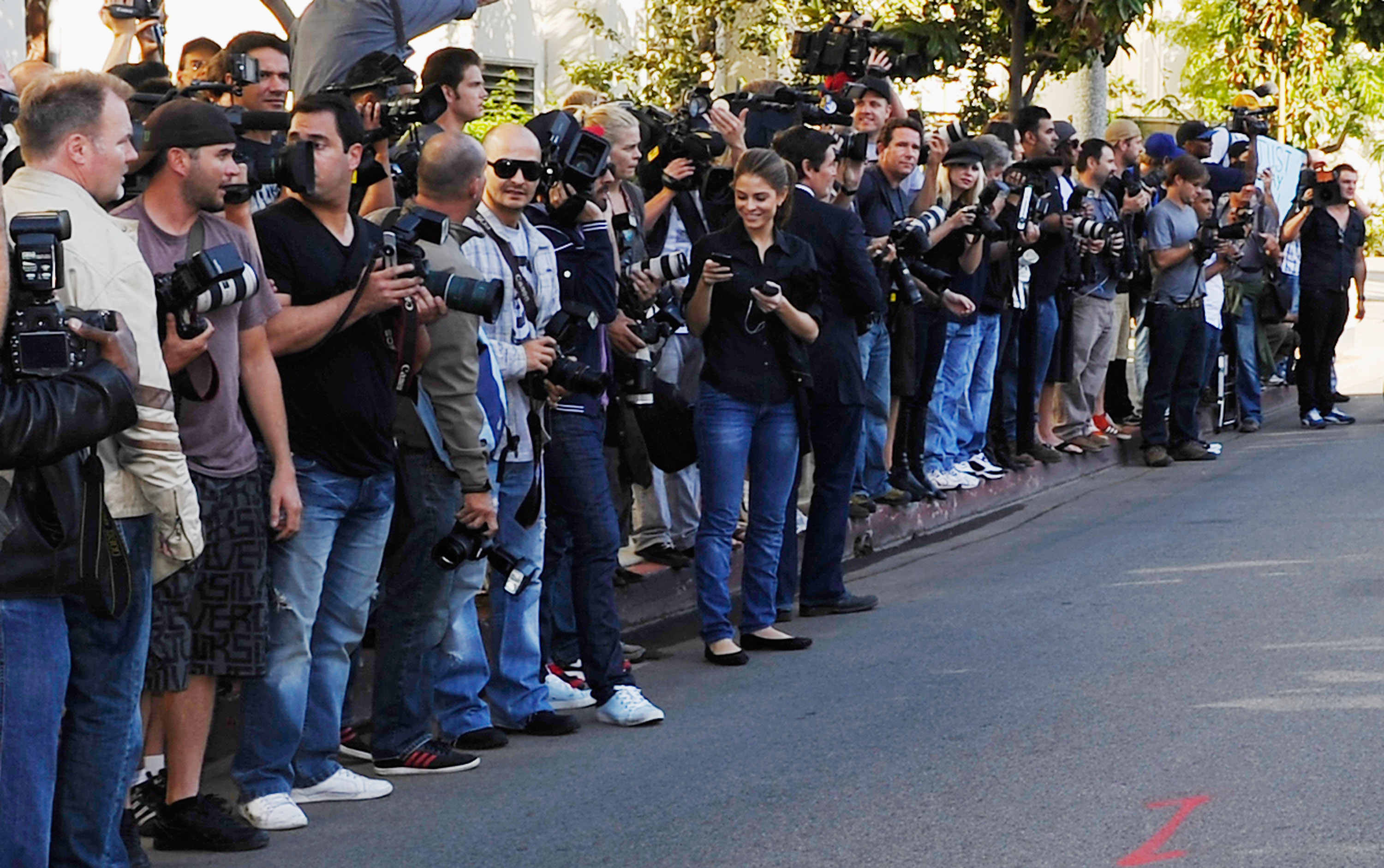 A large group of press photographers stand outside waiting for an event.