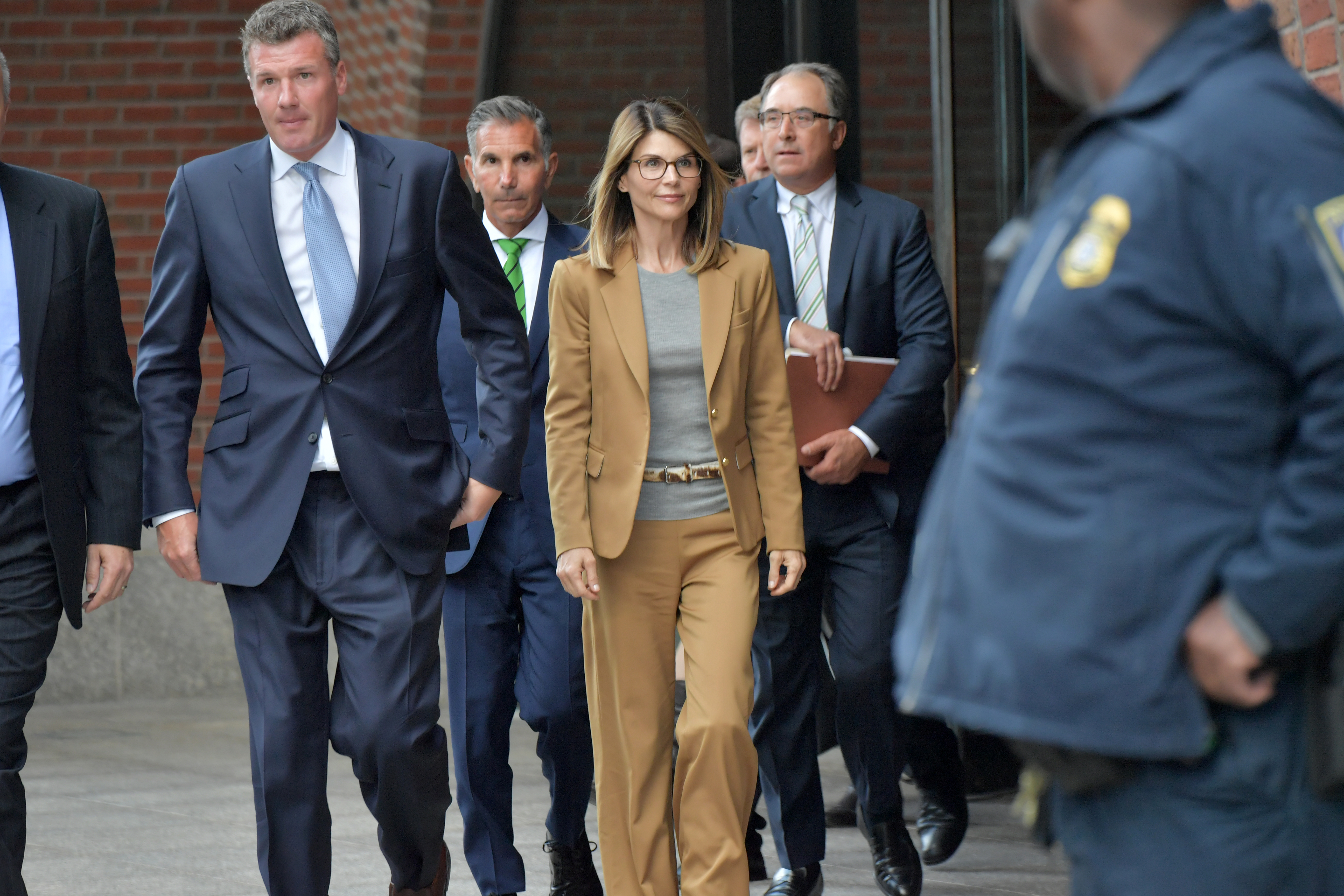 Lori Loughlin and her lawyers walk away from a courthouse.
