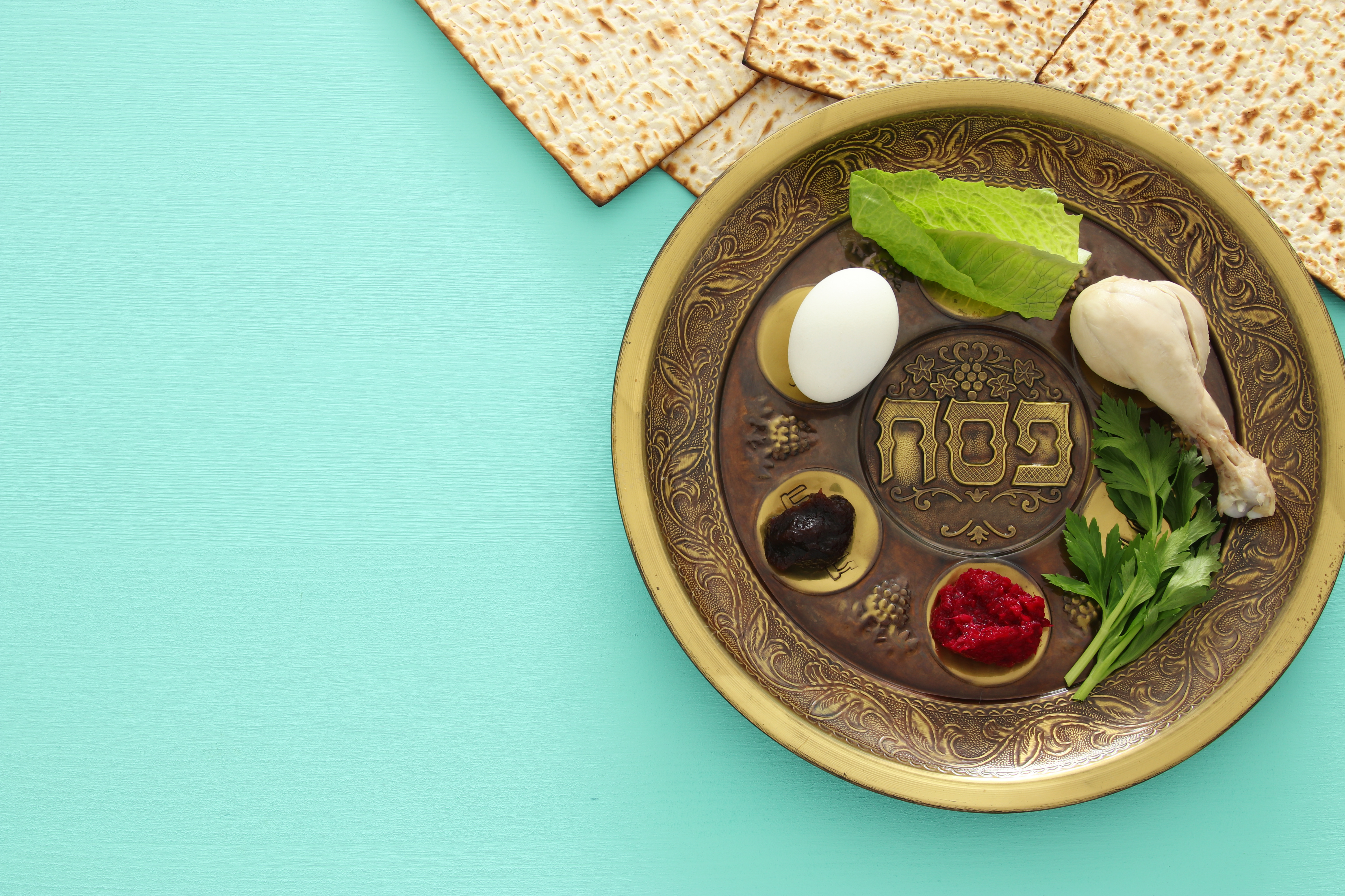 A seder plate with traditional horseradish, celery, egg, bone, maror, and charoset.
