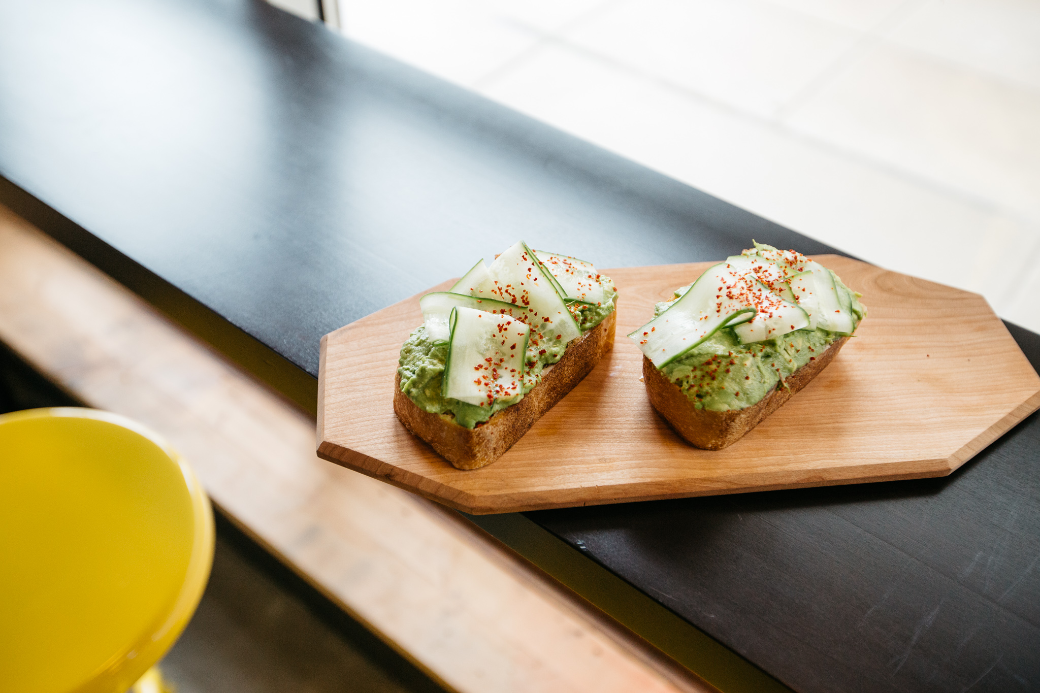 Two slices of avocado toast with cucumber and a sprinkle of red spice sit on a wooden board in a window.