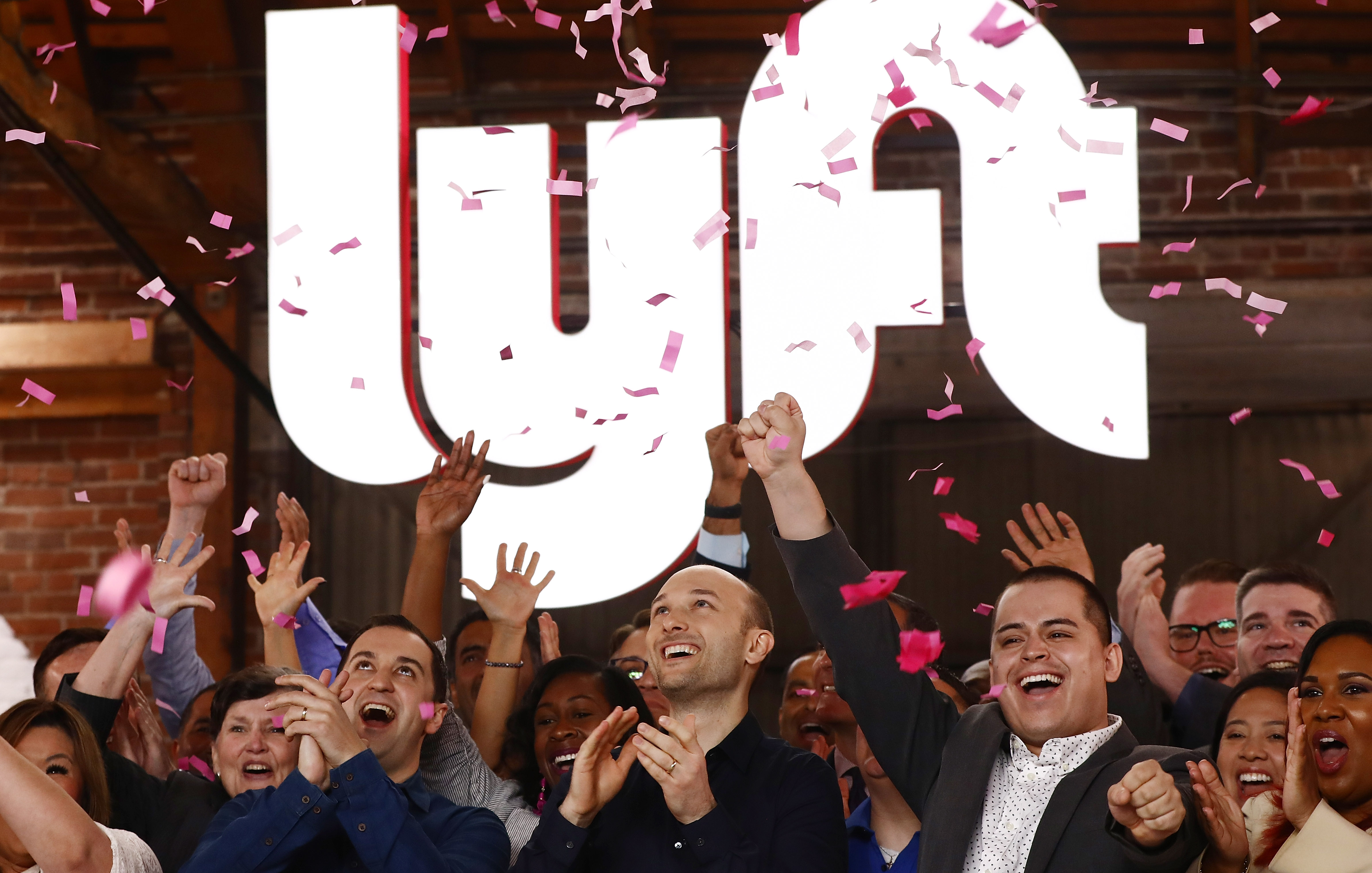 Ride-hailing app Lyft employees at the company's IPO on the Nasdaq stock exchange raise their hands in the air while pink confetti falls on them.