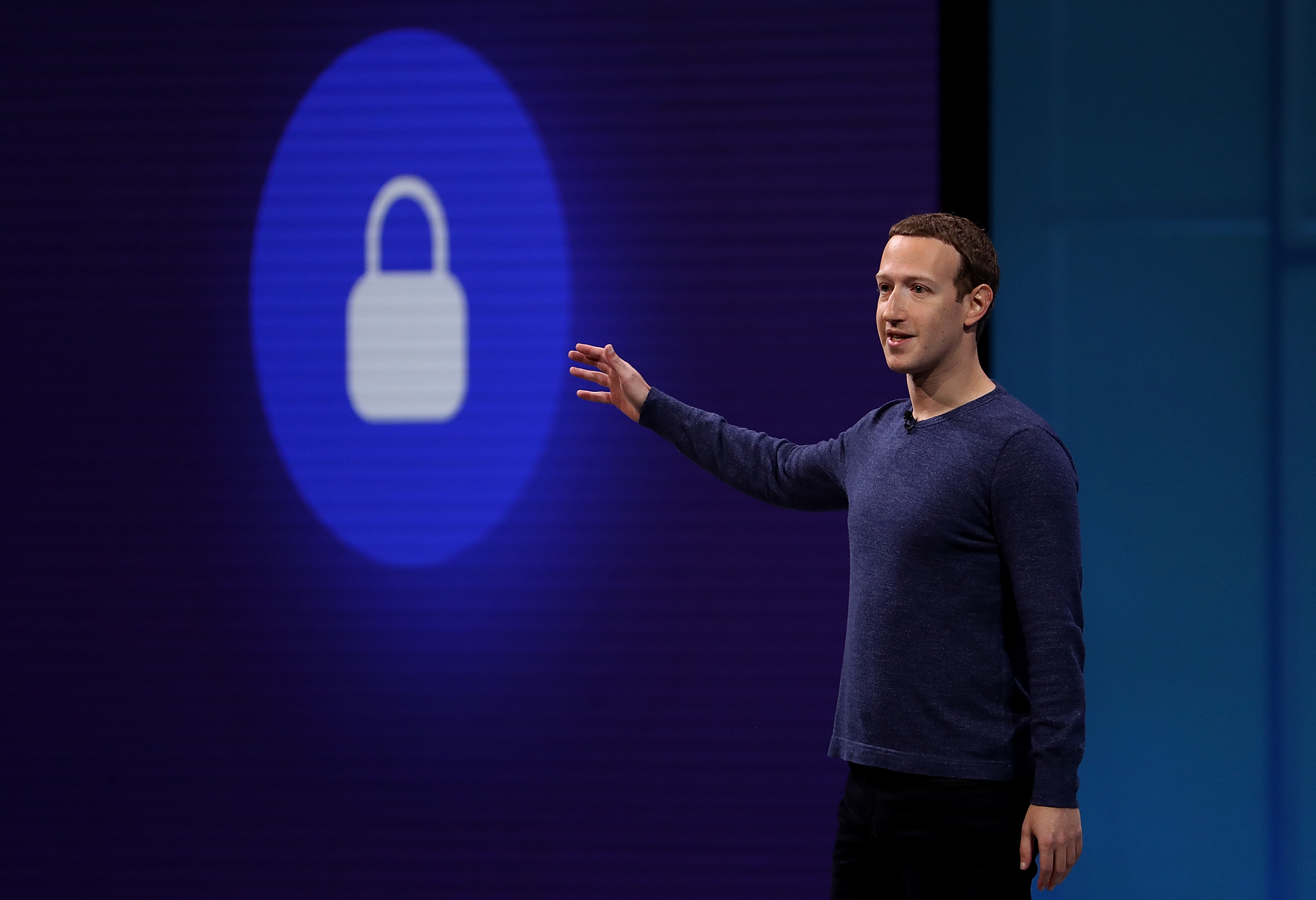 Facebook CEO Mark Zuckerberg onstage gesturing at a picture of a lock.