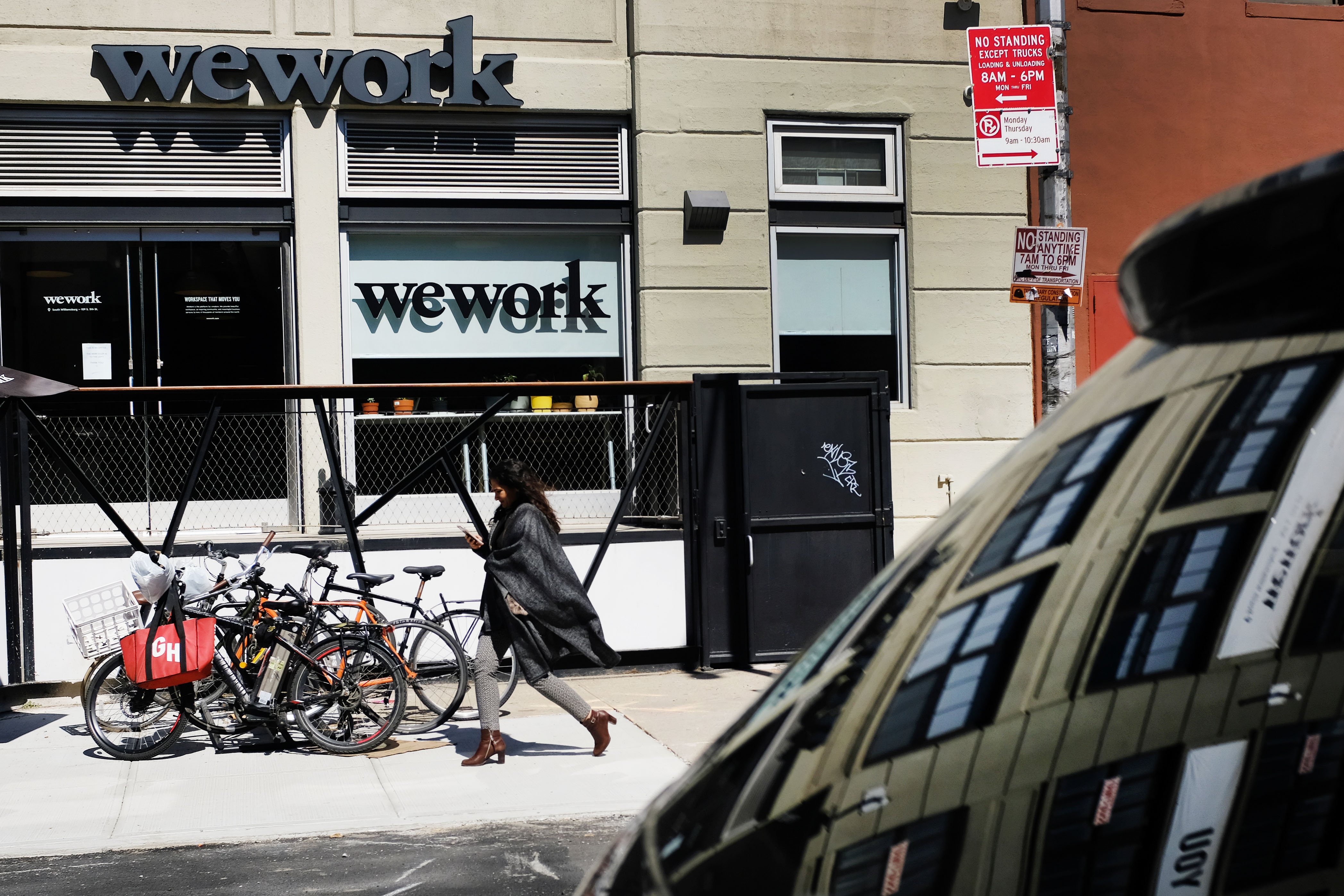 A person on the street walks past a WeWork office's front windows.