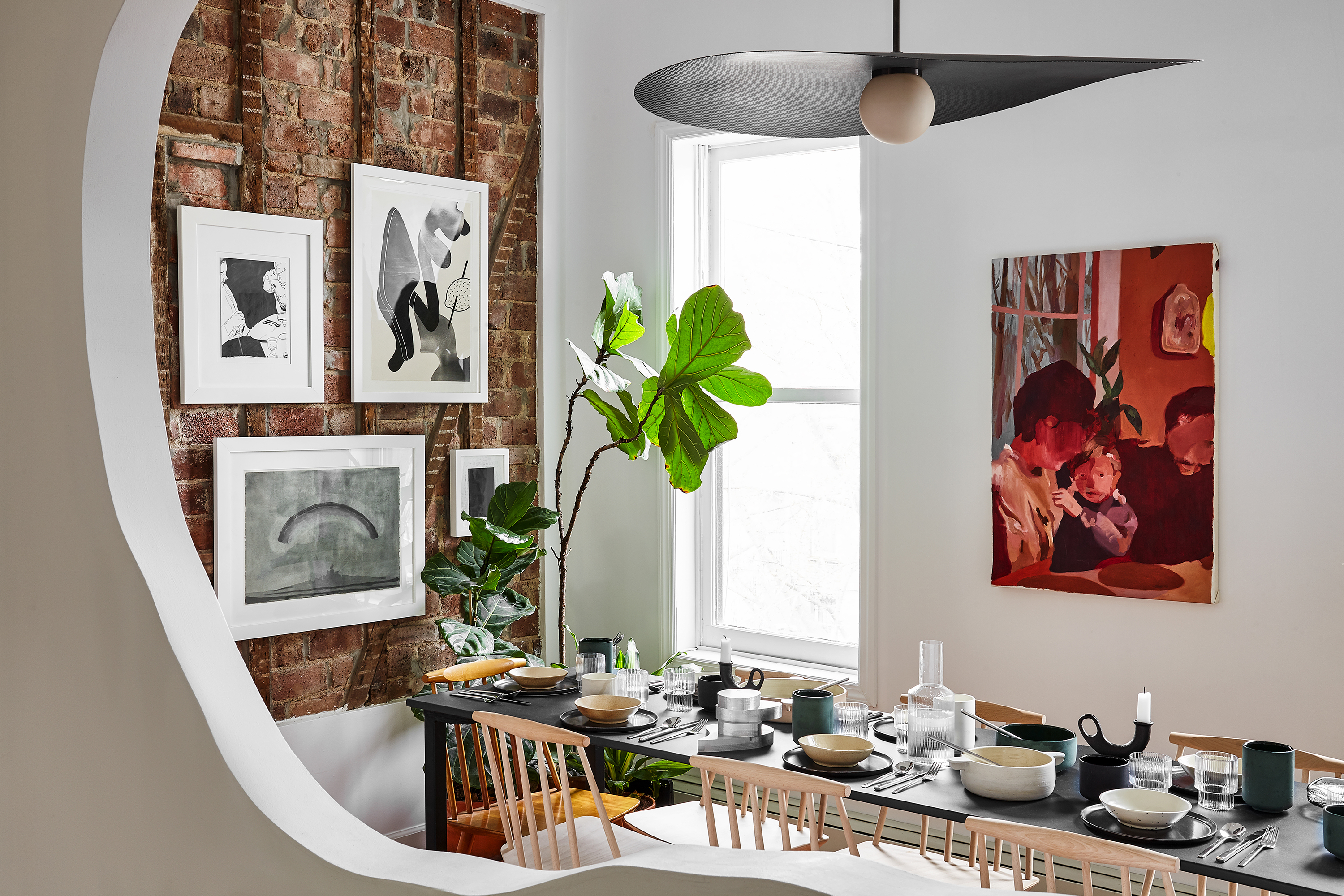 A dining room. One wall is exposed brick and has several framed works of art hanging on it. The other wall is painted white with one work of art hanging on it. There is a long table with chairs. A large houseplant sits next to the brick wall.