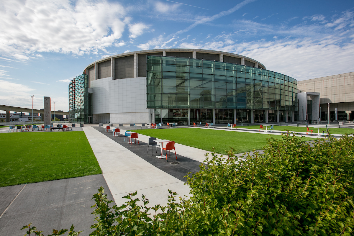 The exterior of the Cobo Center in Detroit. The building is large with many windows. In front of the building is a lawn and walking paths.
