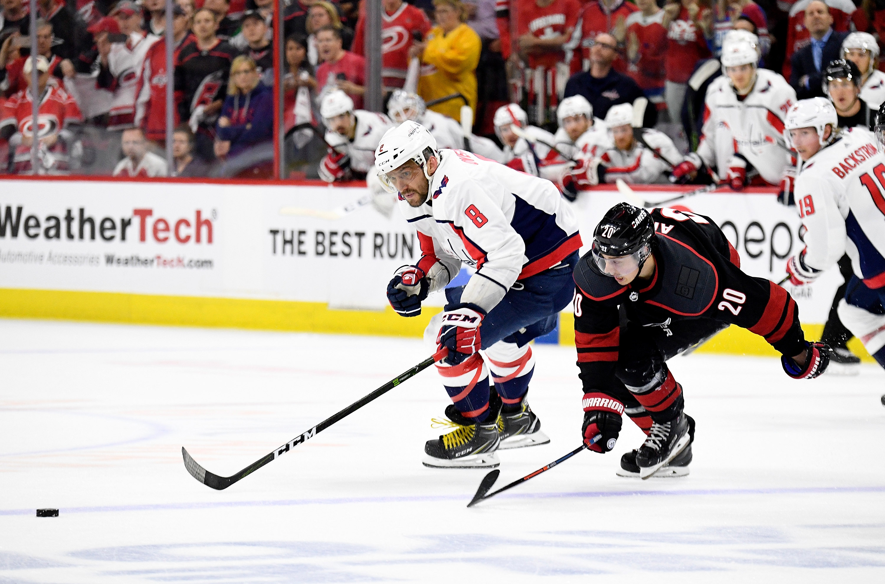 RALEIGH, NORTH CAROLINA - APRIL 18: Alex Ovechkin #8 of the Washington Capitals and Sebastian Aho #20 of the Carolina Hurricanes chase a loose puck in the third period in Game Four of the Eastern Conference First Round during the 2019 NHL Stanley Cup Play