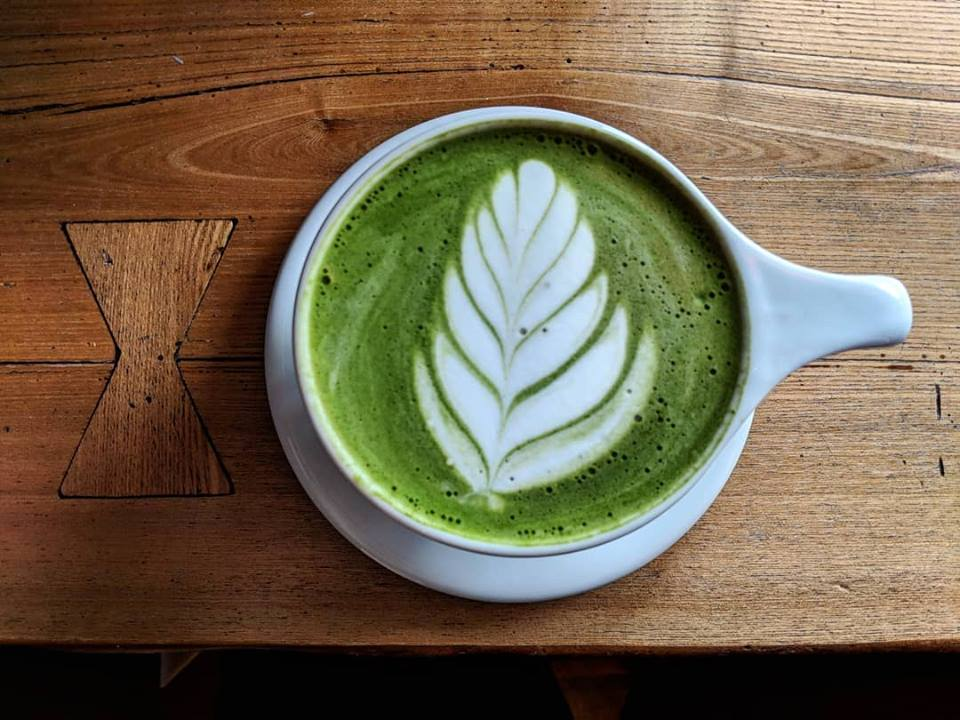 Overhead shot of a bright green matcha latte with fern foam art. It's in a white mug, sitting on a wooden counter top.