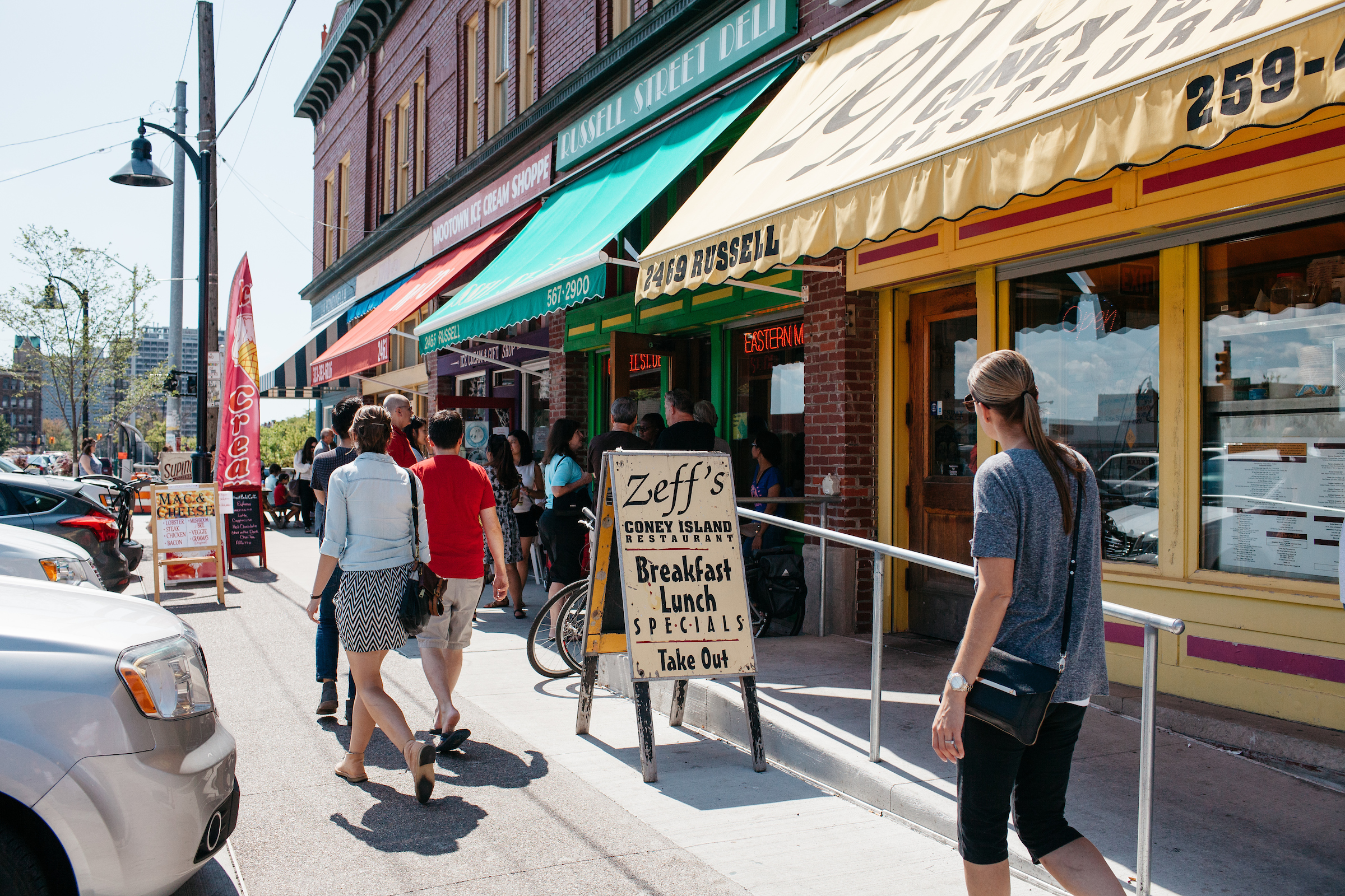 People walk past the yellow awning and sandwich board sign for Zeff's on a sunny day in Eastern Market.