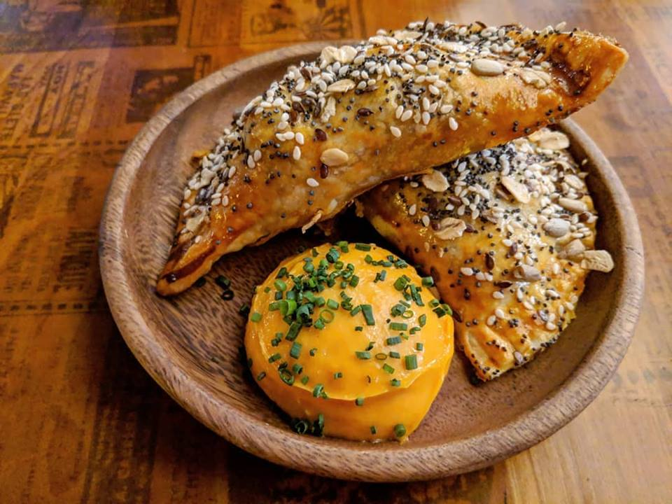 Two empanadas covered with poppyseeds and other seeds sit in a wooden bowl on a table with a surface that looks like newsprint. A thick orange dip sits next to the empanadas.