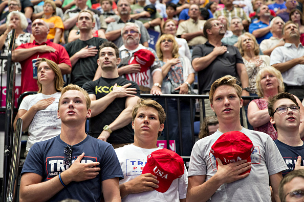 Attendees recite the Pledge of Allegiance before the start of a rally with U.S. President Donald Trump in Cedar Rapids, Iowa, U.S., on Wednesday, June 21, 2017.