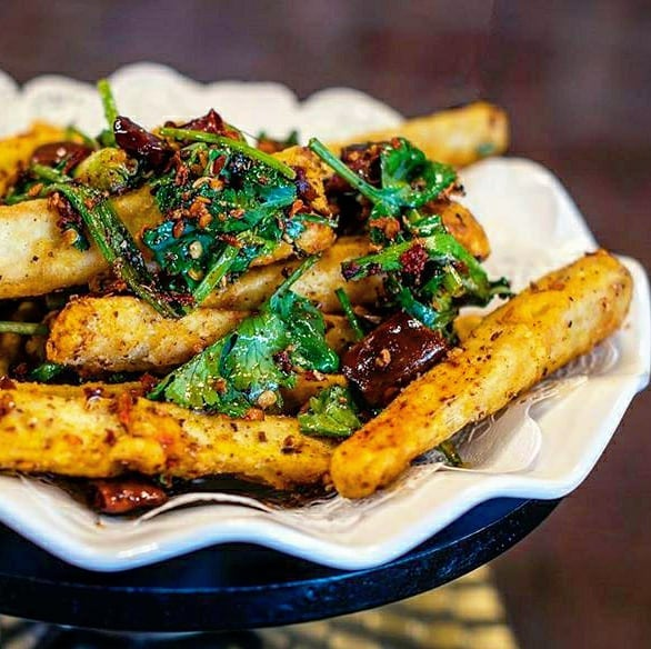 A scalloped-edge white plate with spicy dry-fried eggplant sticks topped with chile peppers and sauteed greens