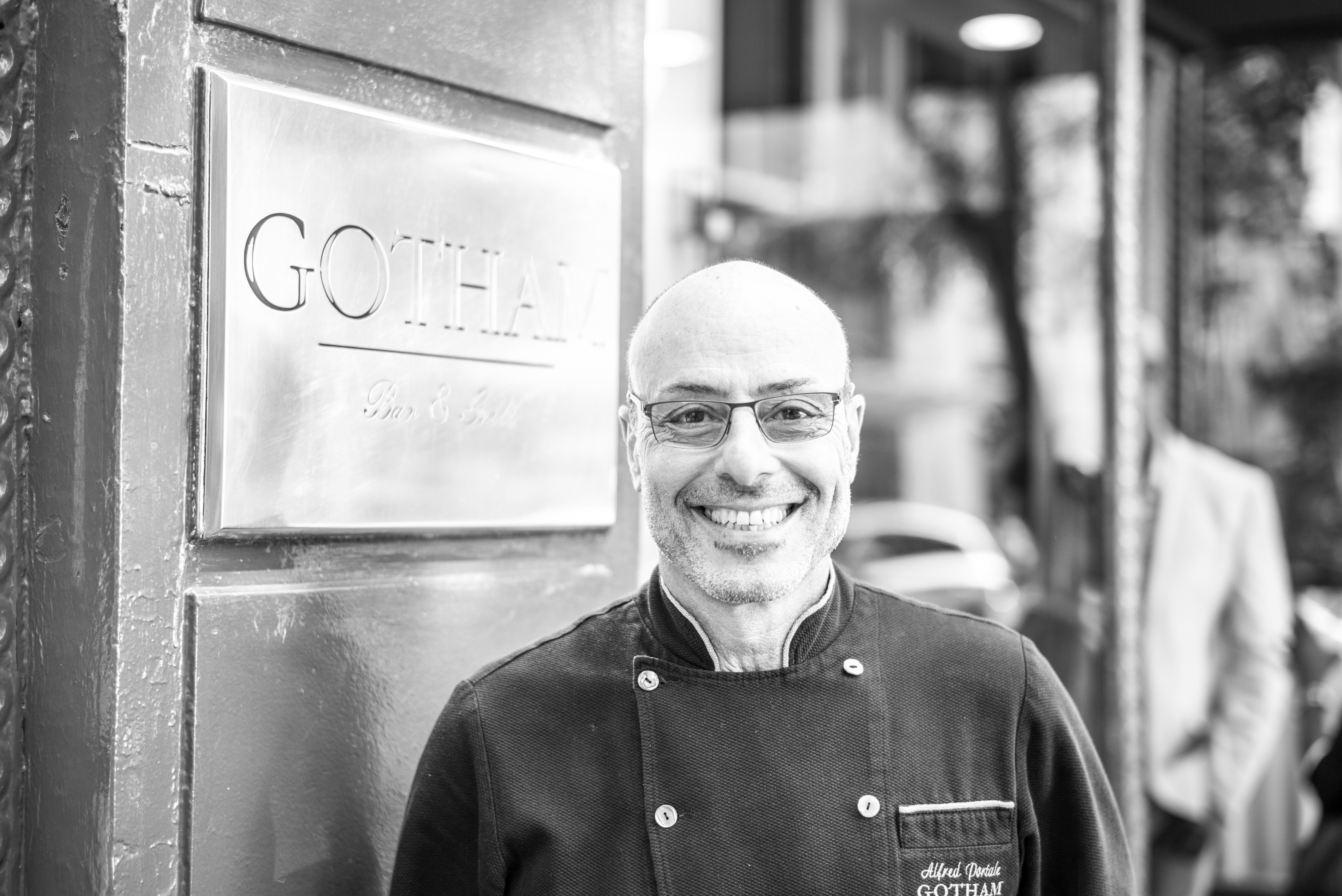 Alfred Portale smiles in front of a sign that says Gotham Bar & Grill
