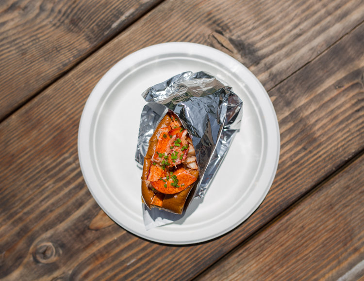 A lobster roll partially wrapped in foil sits on a paper plate atop a wooden table