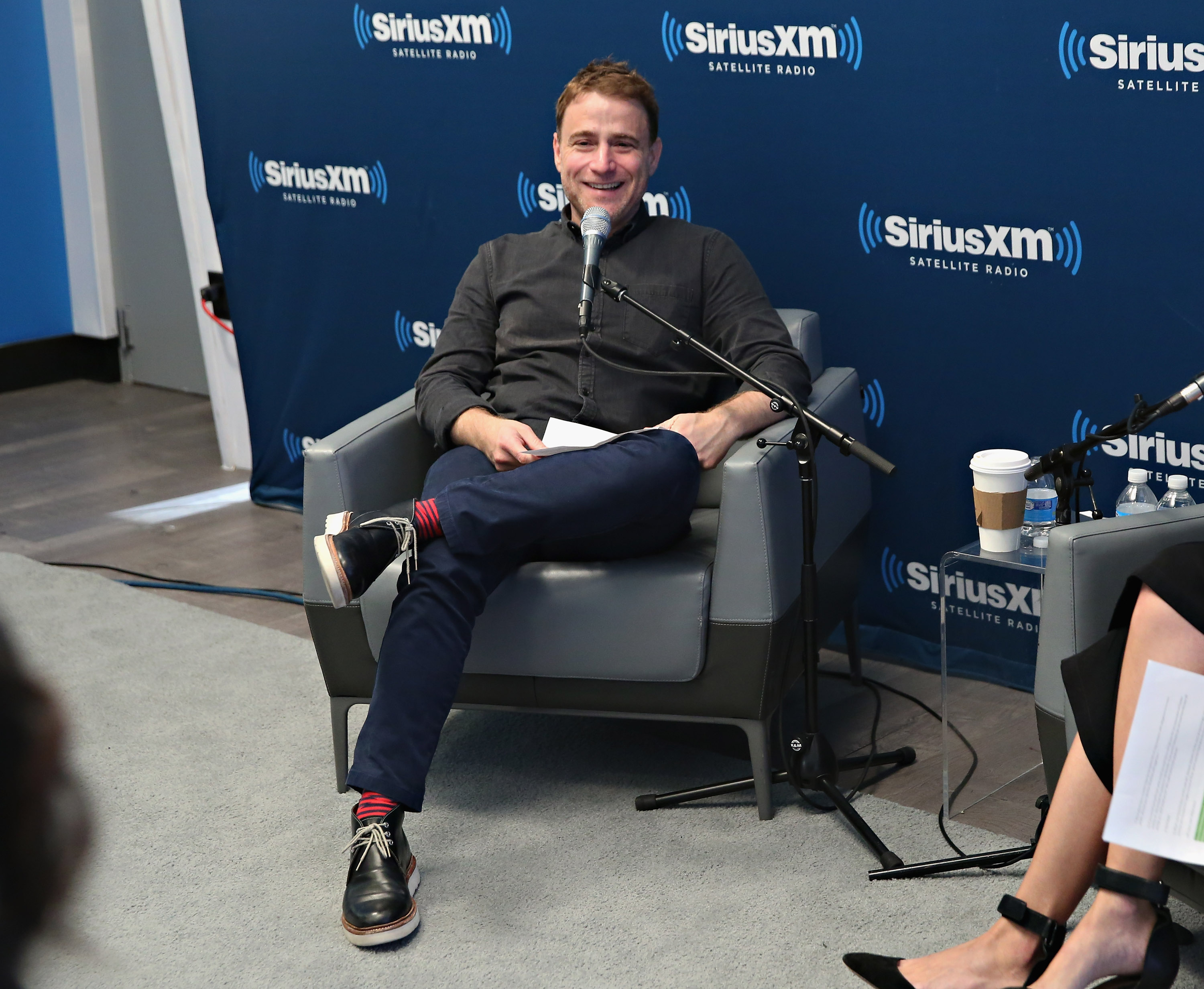 Slack Founder Stewart Butterfield speaking from a chair on the set of a SiriusXM radio broadcast.