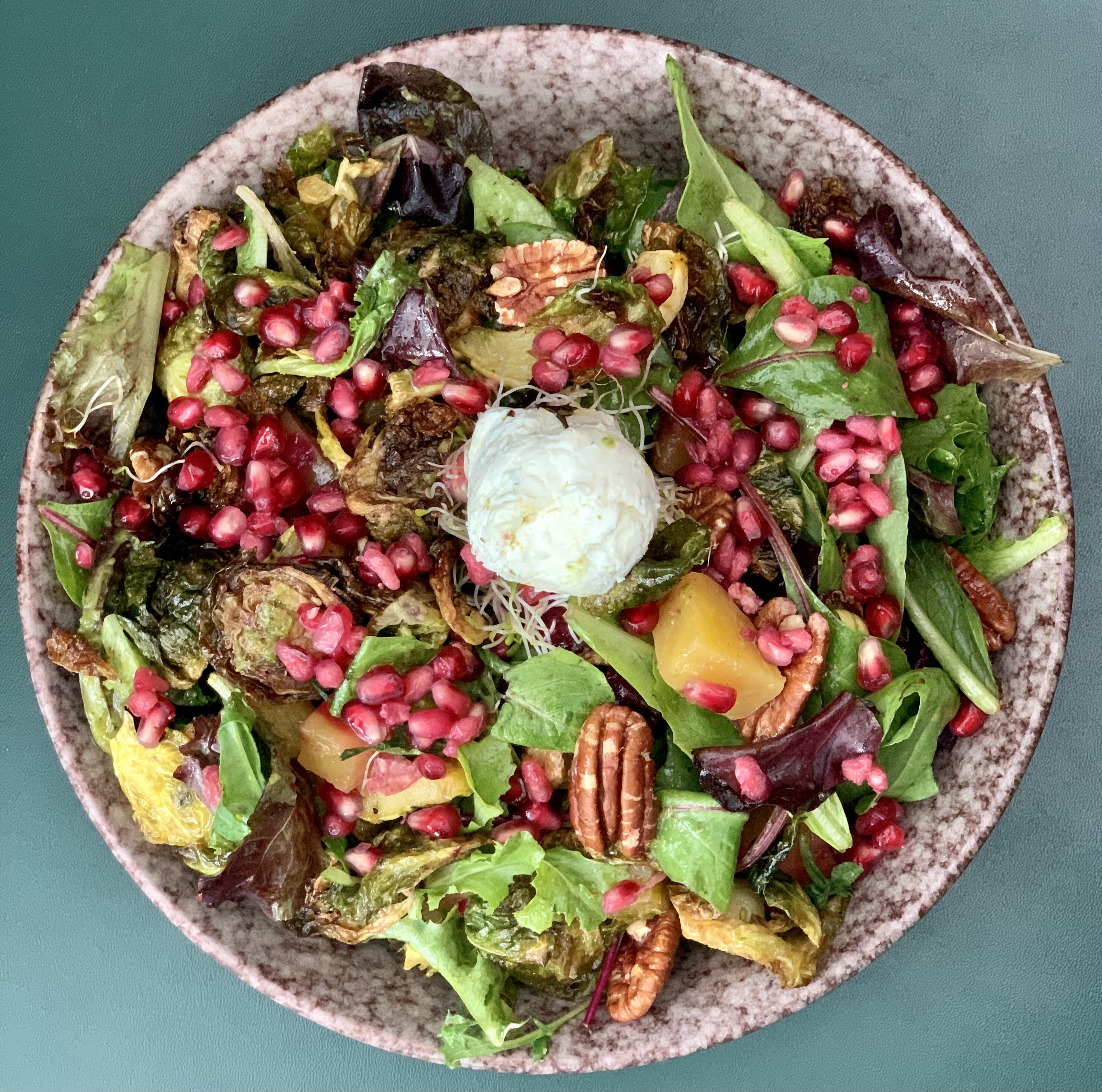 a green leafy salad with squash, pecans and pomegranate seeds