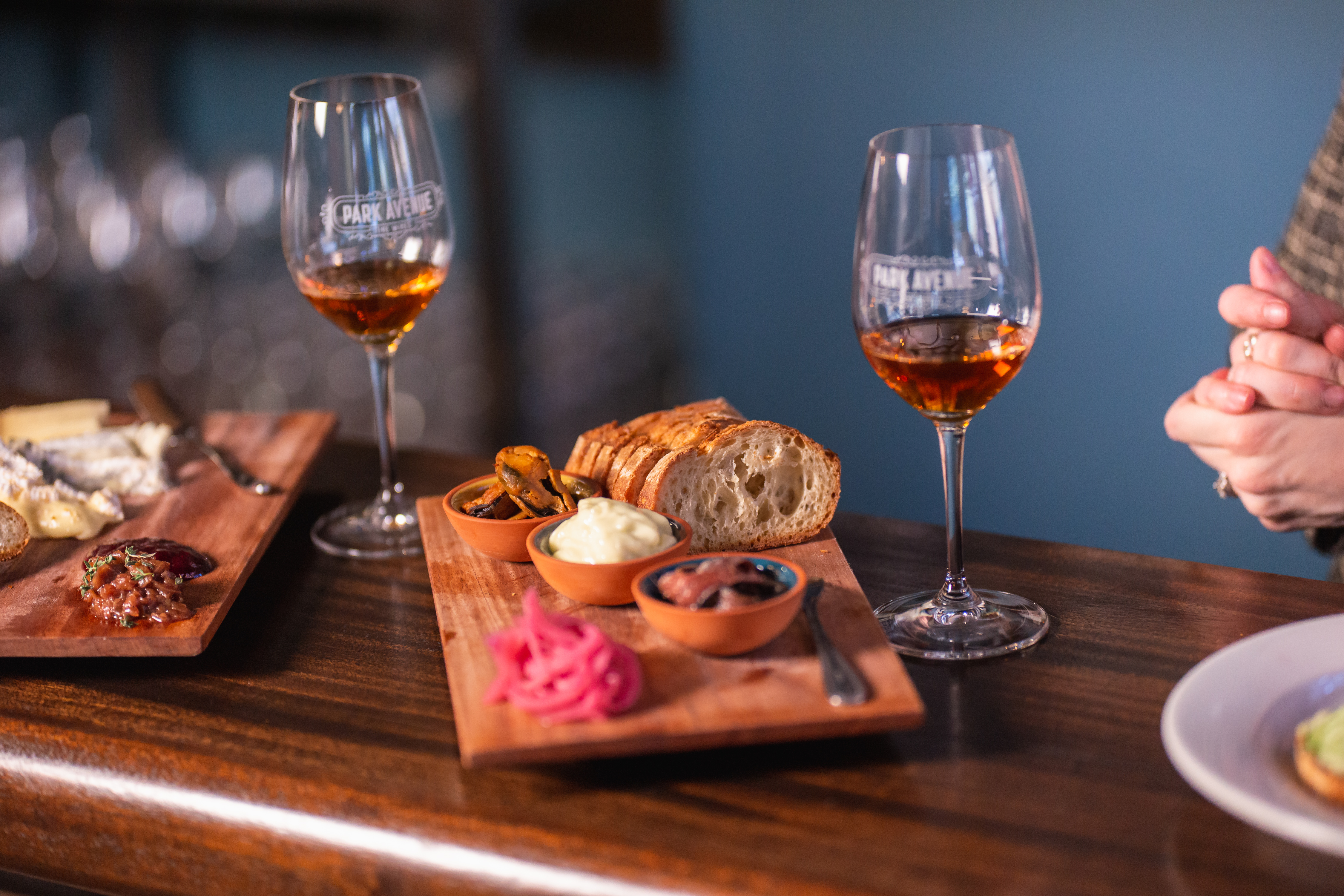 A cheese board sits on a bar between two glasses of dark copper-colored wine