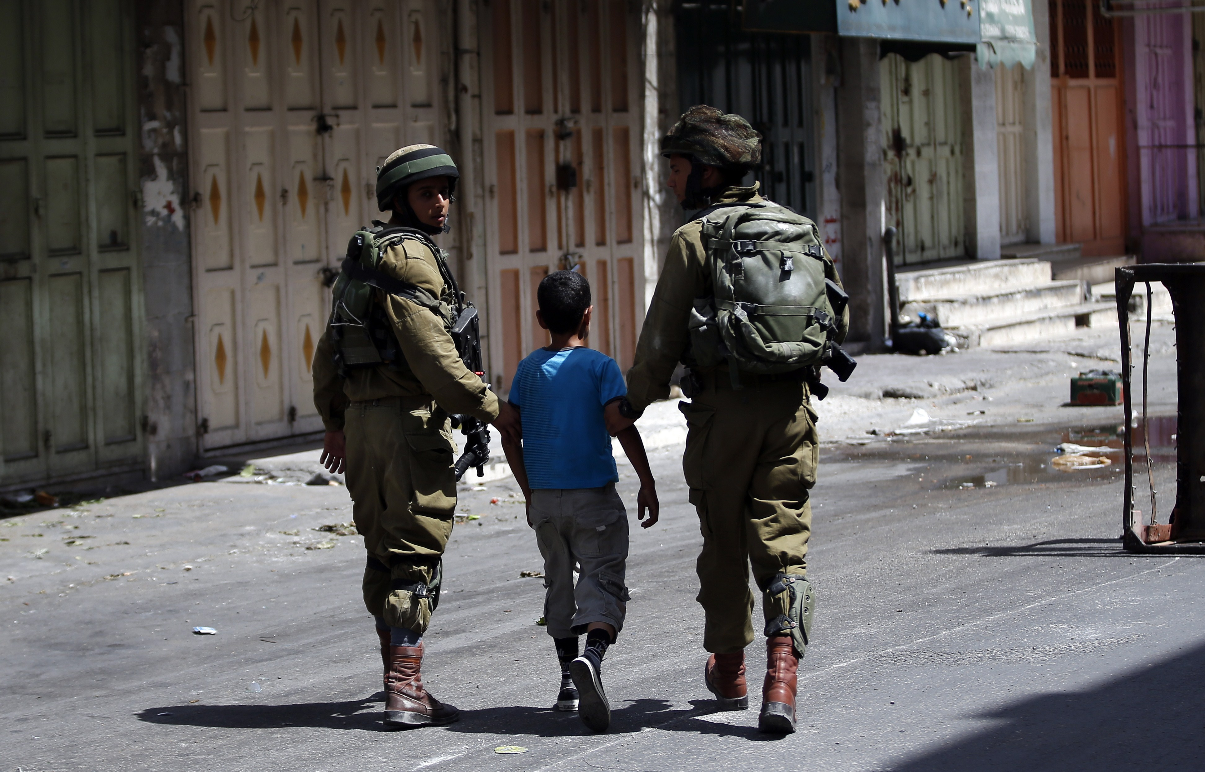 Israeli soldiers arrest a young Palestinian boy following clashes in the center of the West Bank town of Hebron, on June 20, 2014.