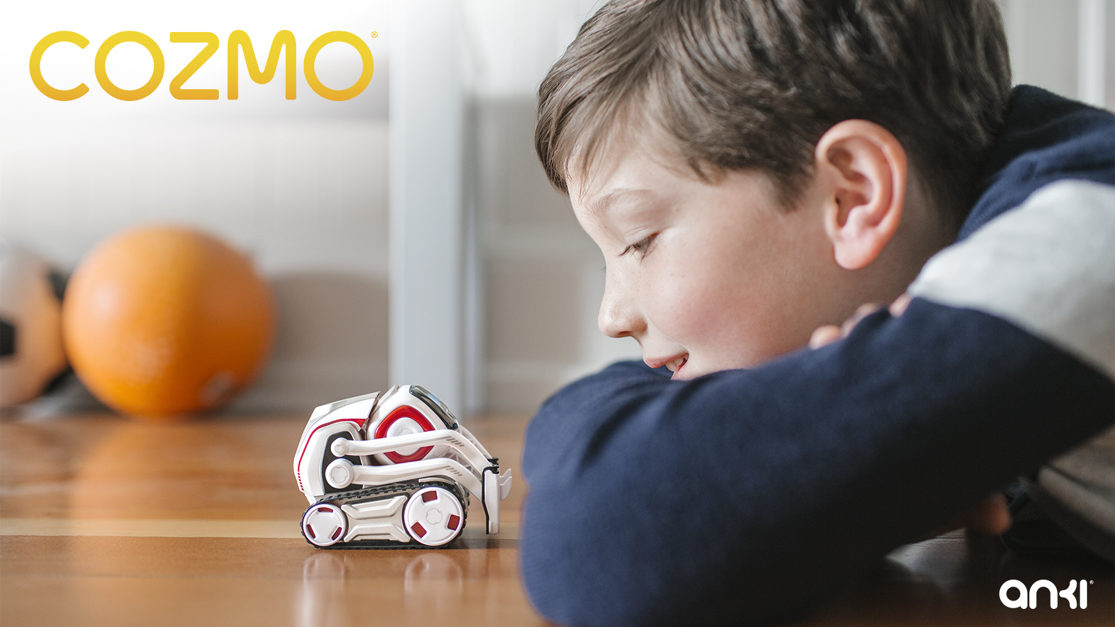 A young boy lies face to face on the floor with a Cozmo robot.