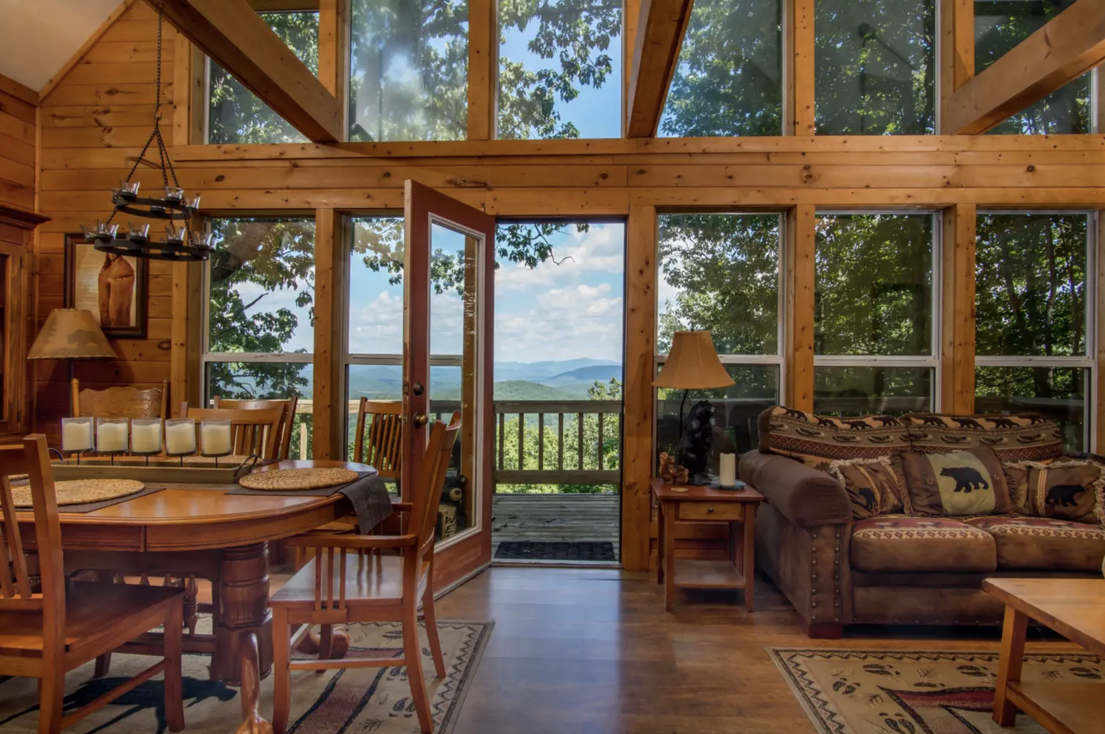 Mountain views from the floor-to-ceiling windows of a cabin living room with couch, table and chairs.