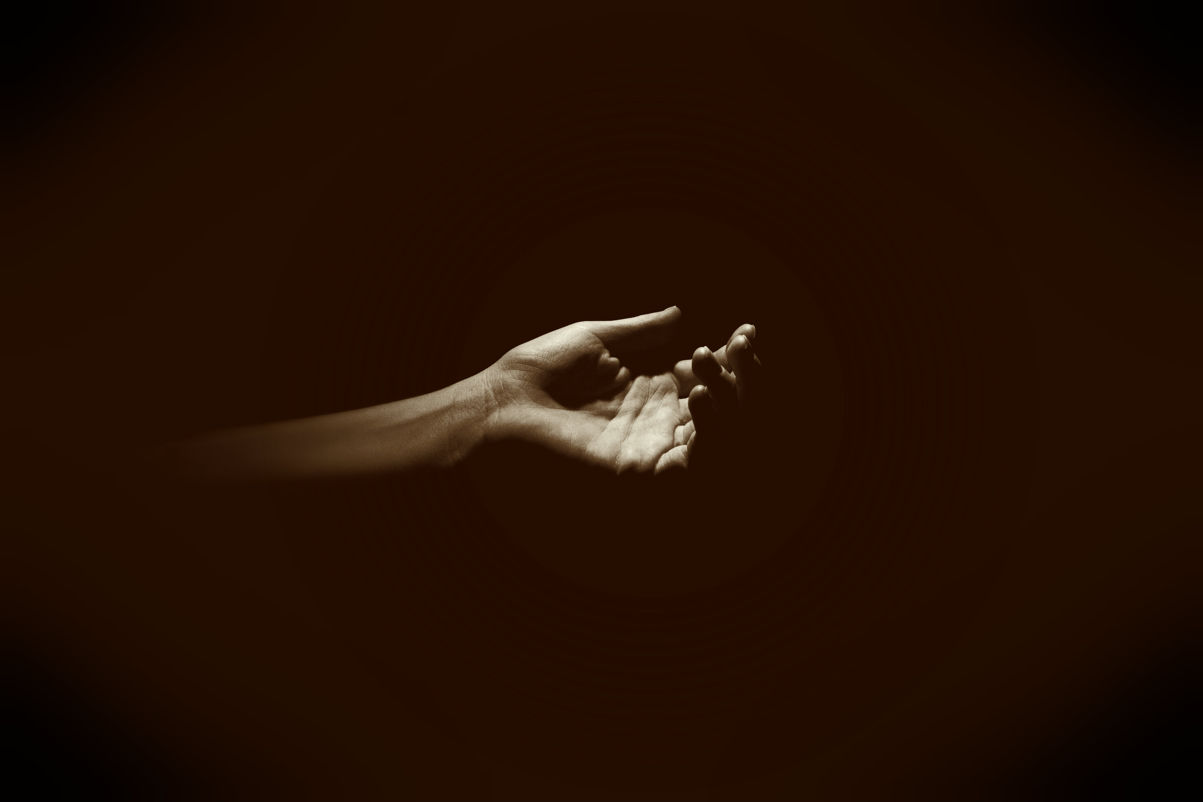 A hand in darkness.