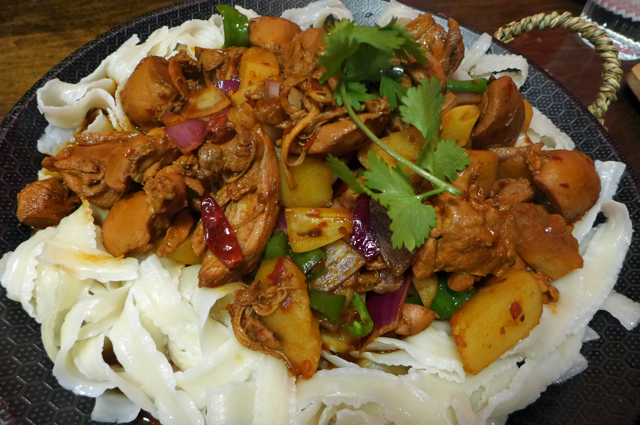 Wide homemade noodles with stewed chicken and potatoes on top.