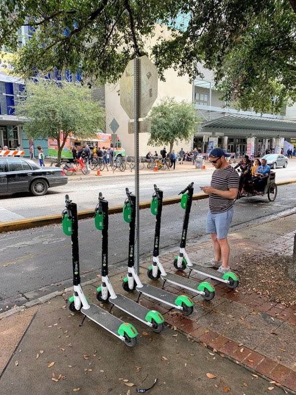 Man with phone standing by Lime scooters on sidewalk