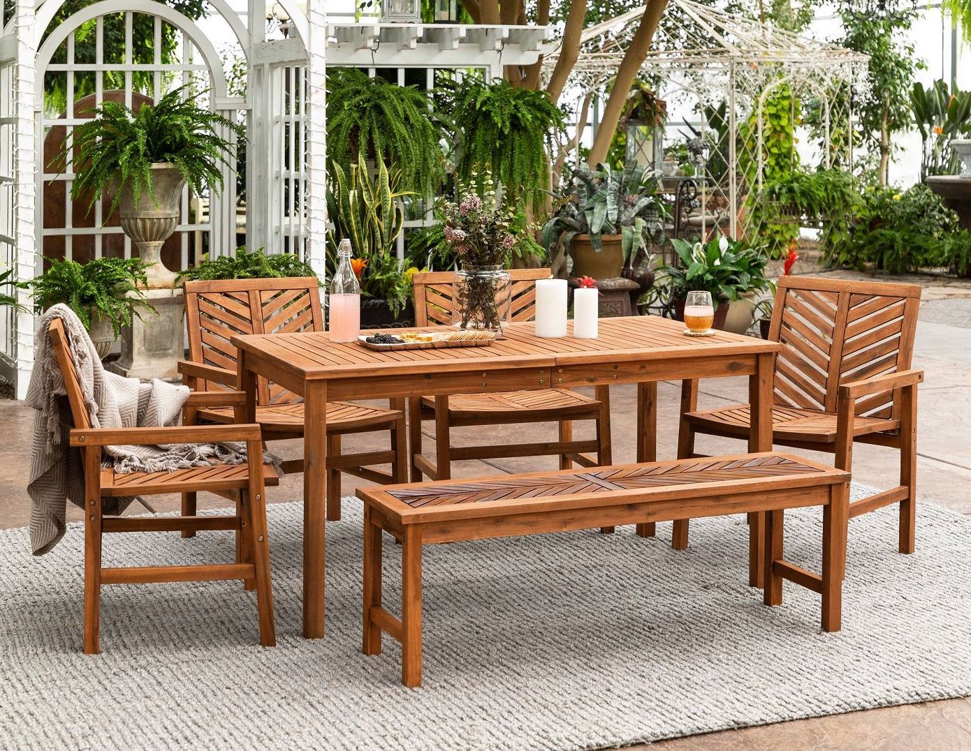 A six-person wood outdoor dining table with four chairs and a bench.
