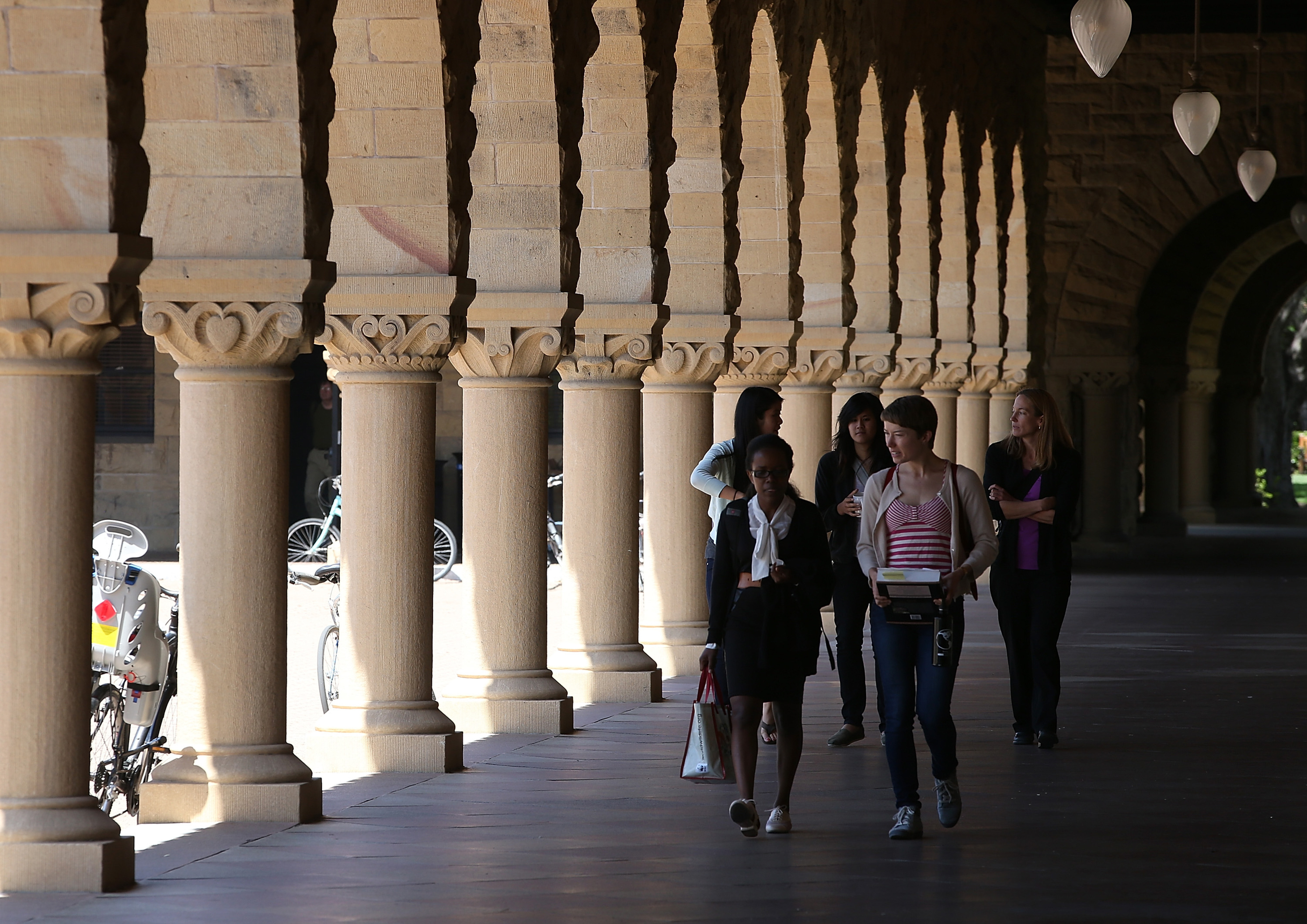 Students on the Stanford University campus walk down a pillared archway.