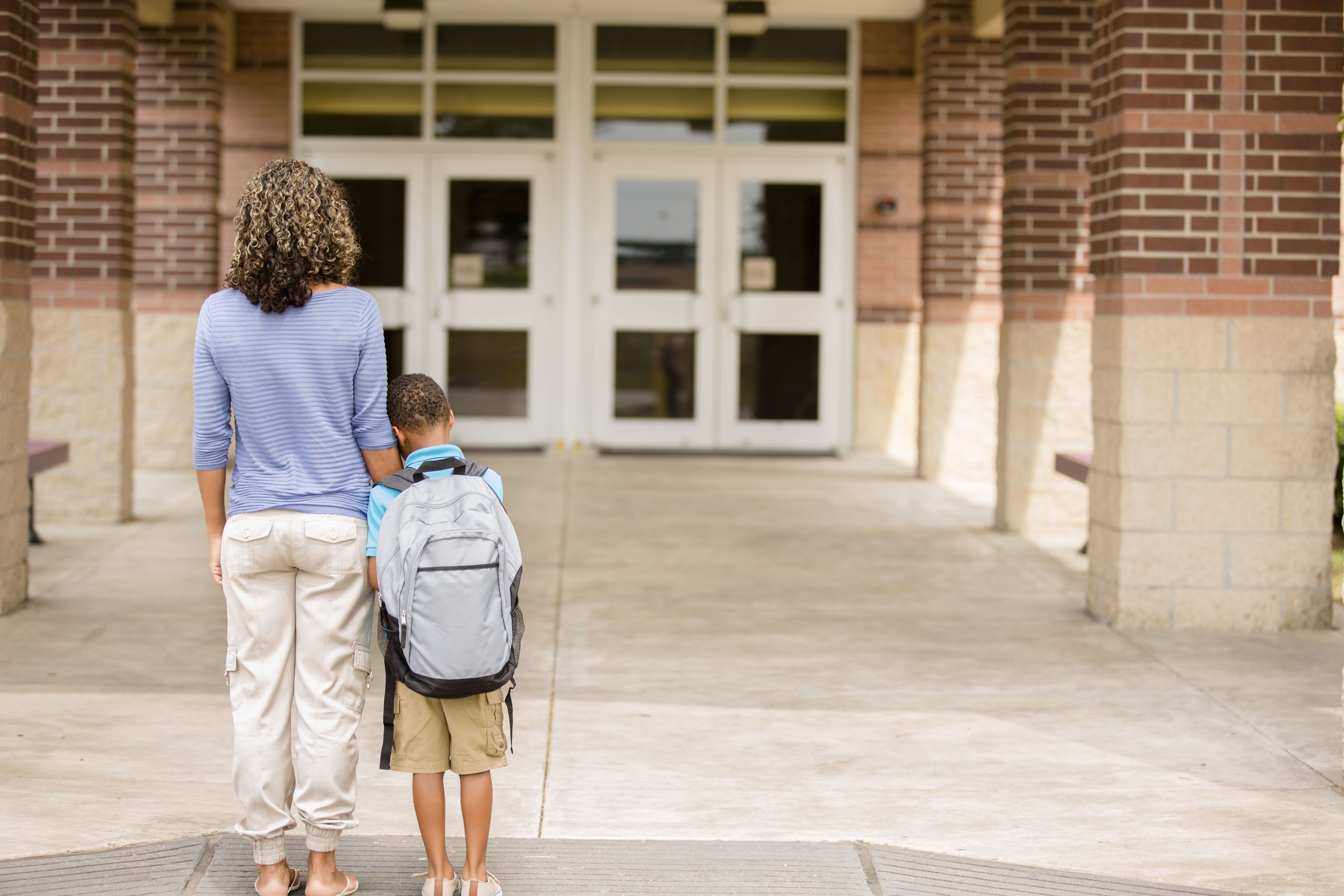 A mother and child stand together outside a school building.