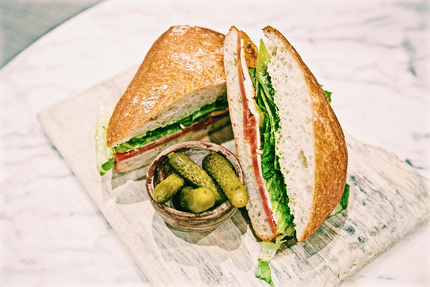 A sandwich on a plate with a bowl of cornichons