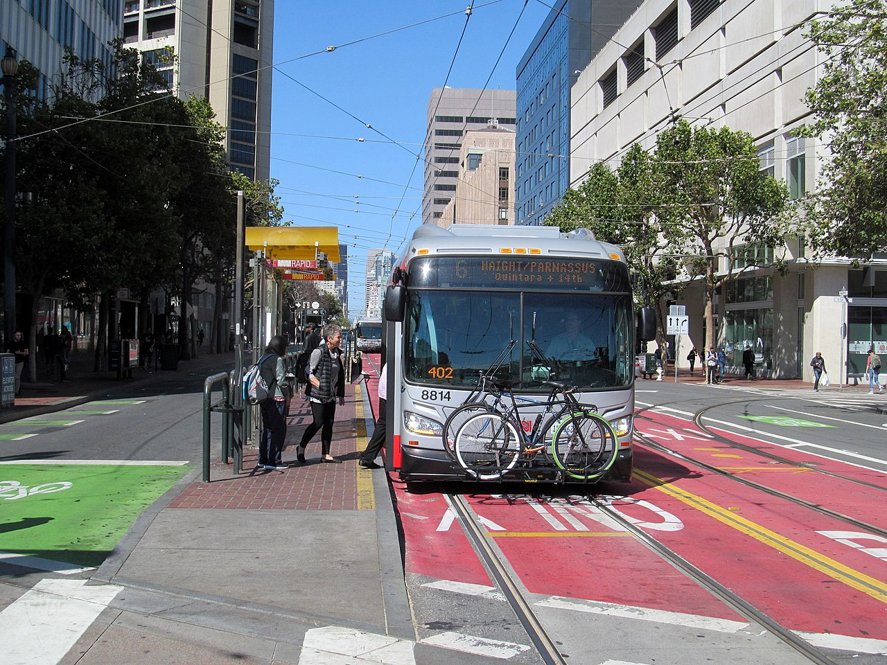 A bus pulling up to a Market Street stop in a red transit-only lane.