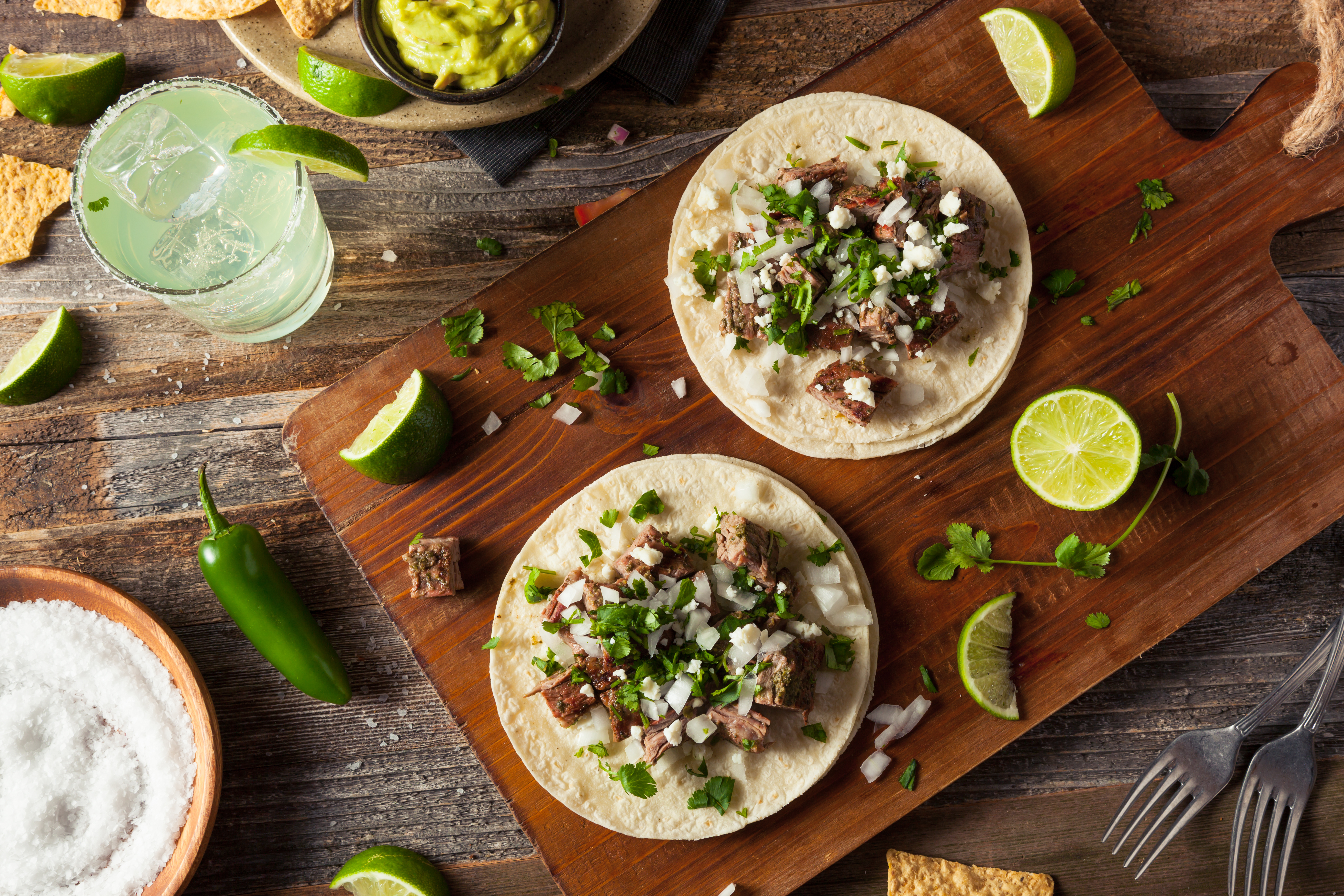 Tacos with salsa and limes with margaritas on a wooden table.