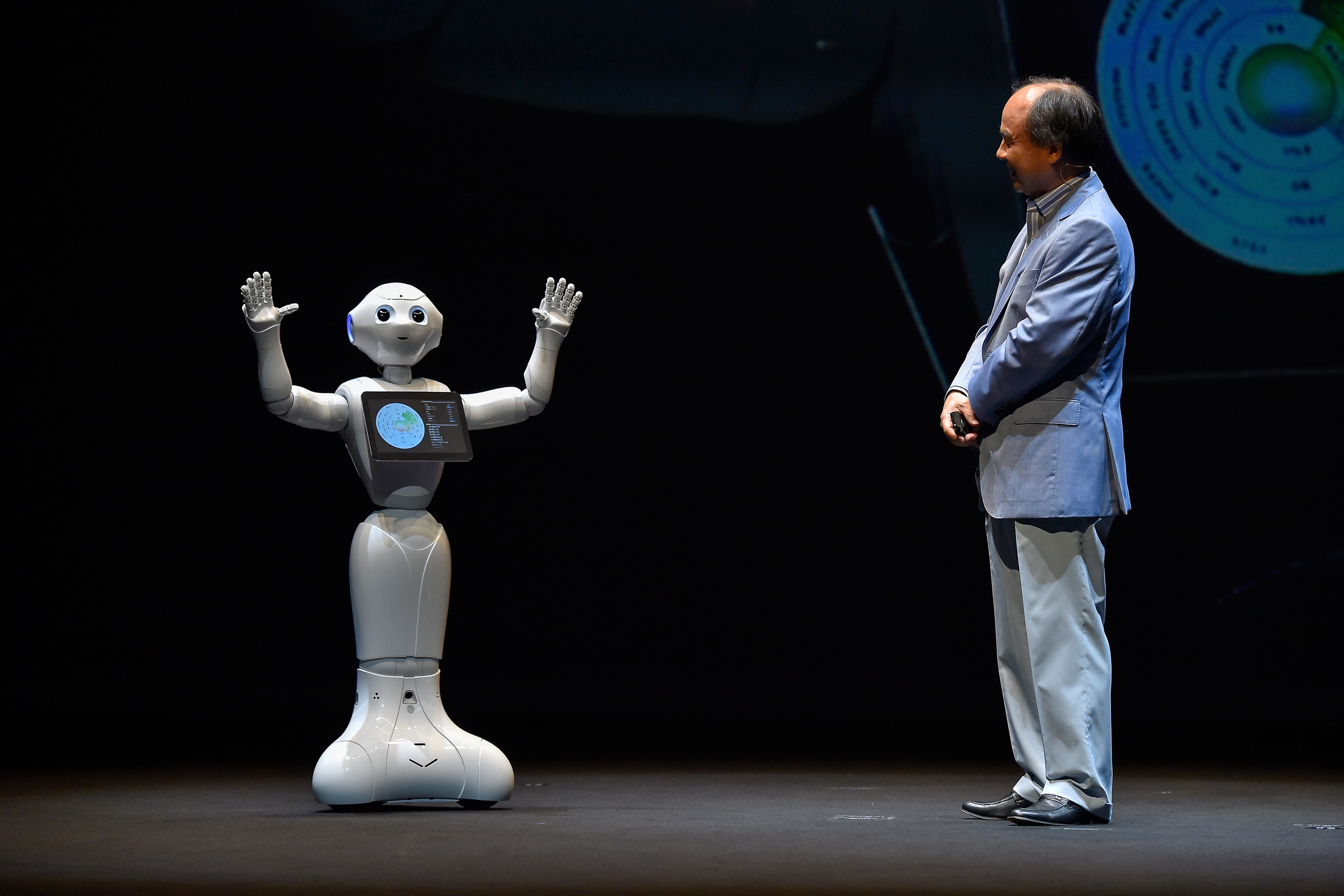 SoftBank CEO Masa Son onstage with Pepper the humanoid robot assistant.