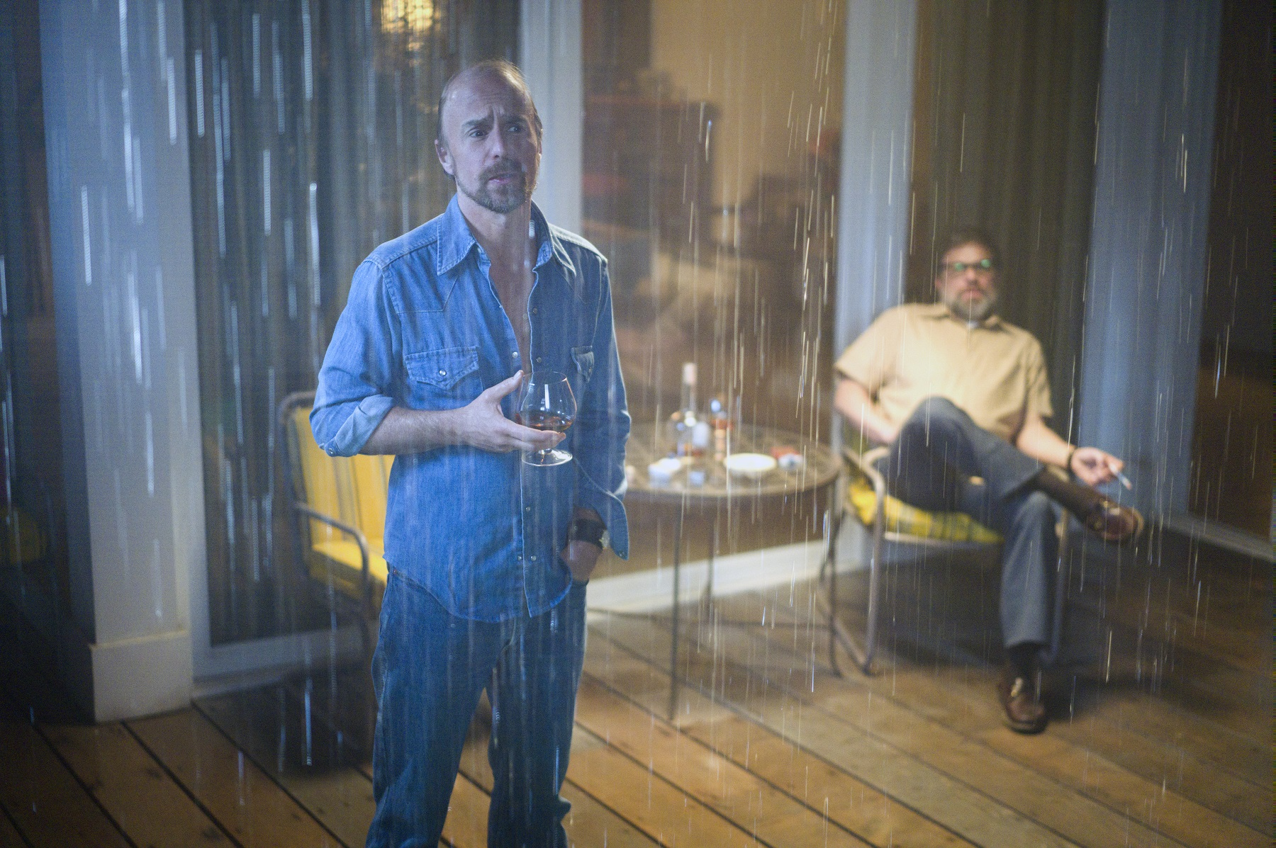 """A scene from the FX show """"Fosse/Verdon"""" where two characters are outside drinking brandy on the deck of a beach house in the rain."""